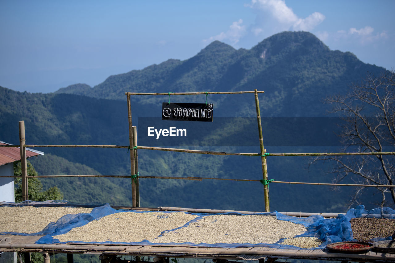 mountain, text, communication, sky, western script, sign, guidance, nature, information, information sign, no people, day, mountain range, blue, sunlight, safety, outdoors, barrier, scenics - nature, script
