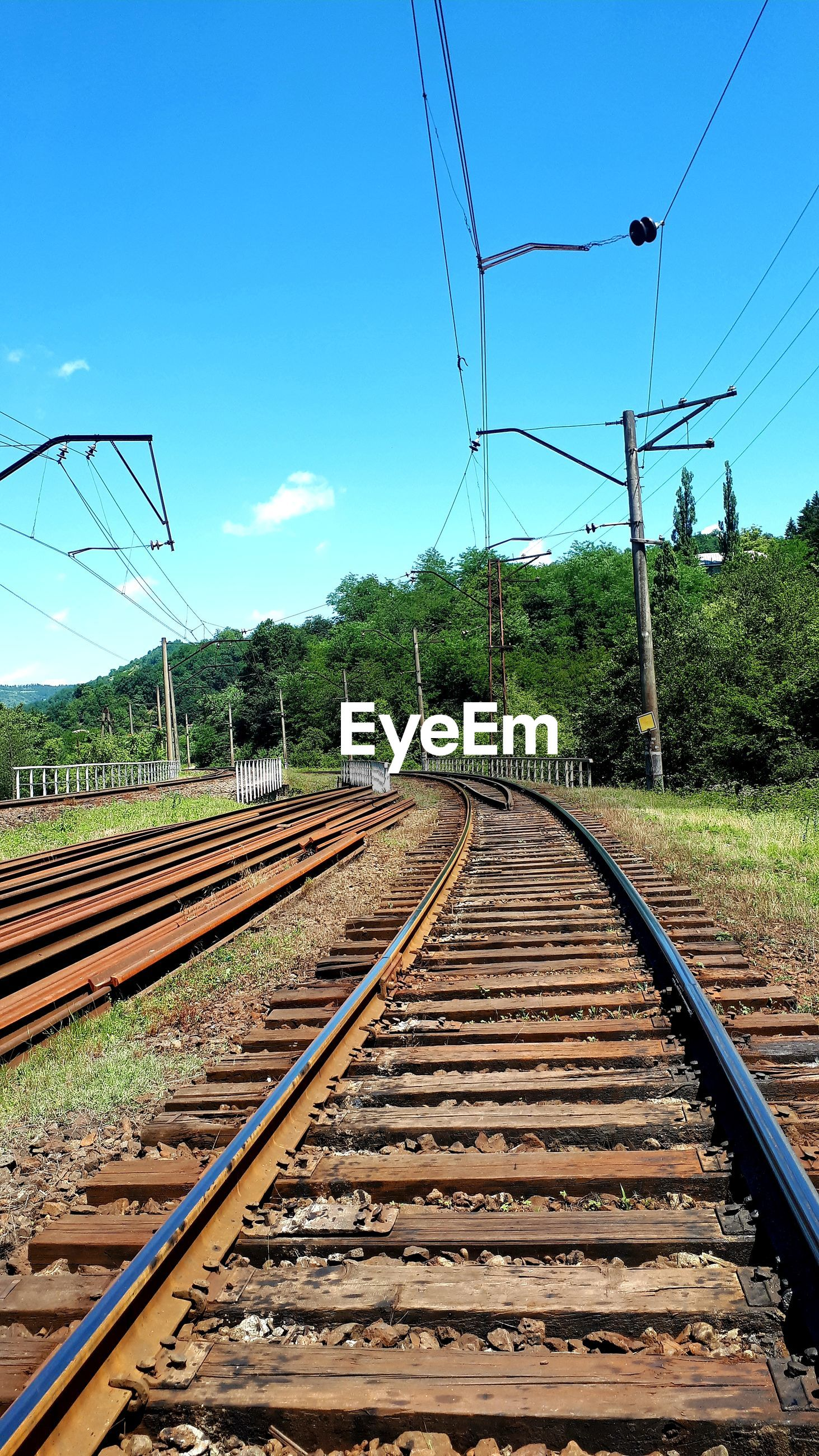 Diminishing perspective of railroad tracks against blue sky