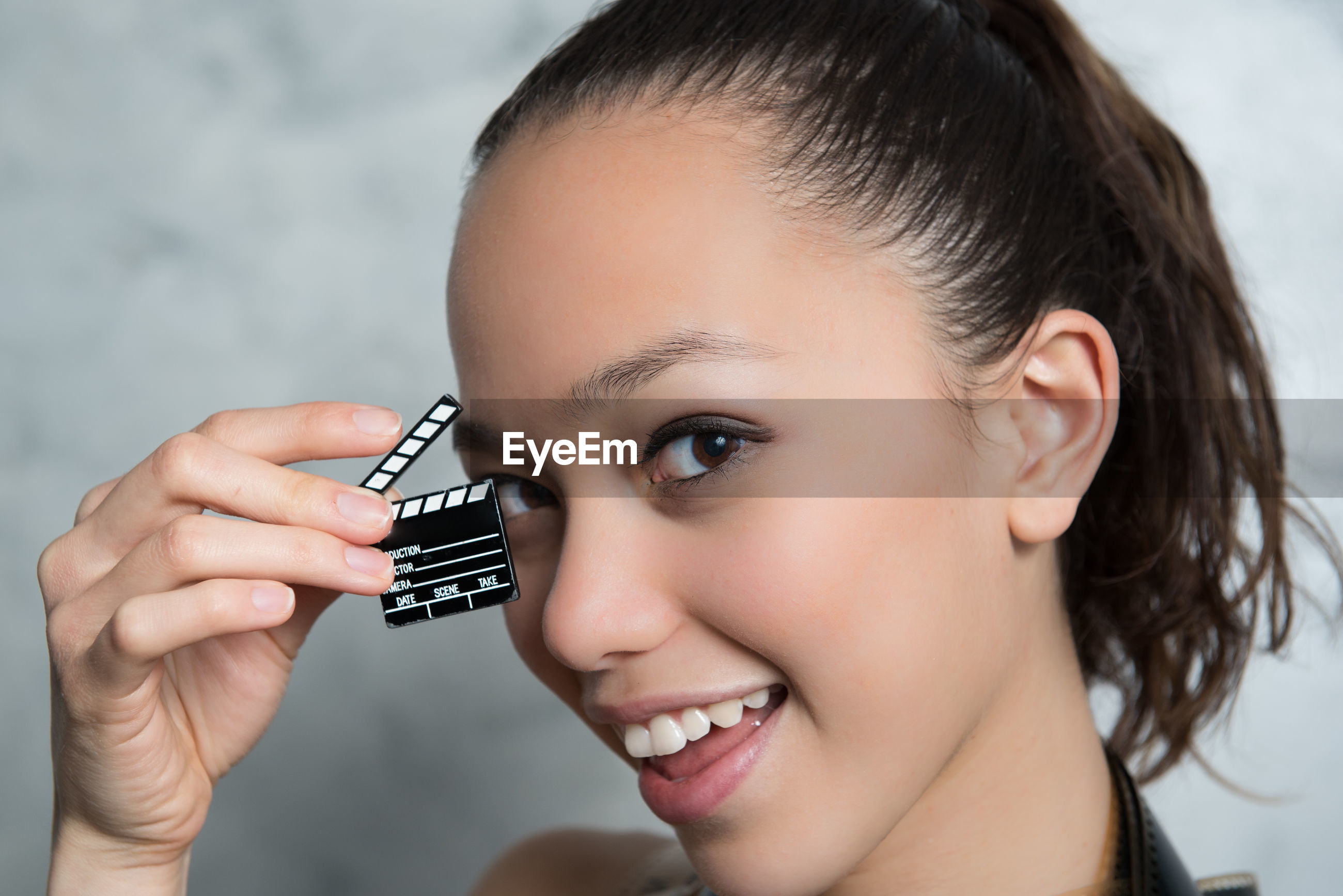Close-up portrait of beautiful fashion model holding miniature film slate