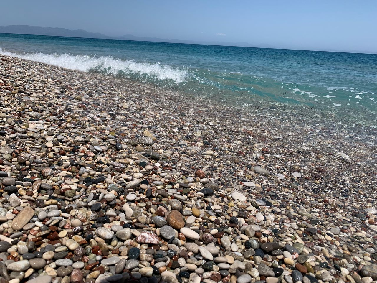 water, sea, beach, pebble, beauty in nature, stone, solid, rock, land, scenics - nature, horizon over water, horizon, nature, stone - object, tranquil scene, tranquility, sky, day, no people, outdoors, shallow