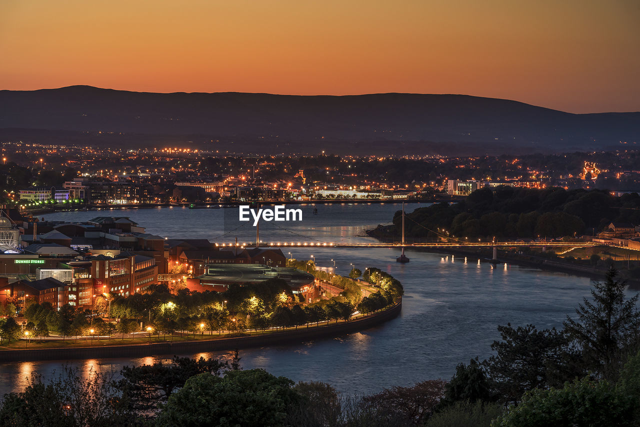 architecture, built structure, illuminated, building exterior, river, cityscape, water, sunset, city, connection, high angle view, tree, no people, bridge - man made structure, outdoors, sky, night, waterfront, travel destinations, chain bridge, nature, scenics, mountain, beauty in nature