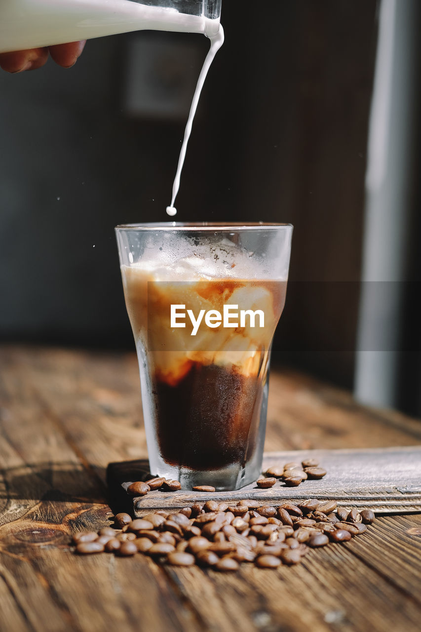 Cropped Hand Pouring Milk In Iced Coffee On Wooden Table