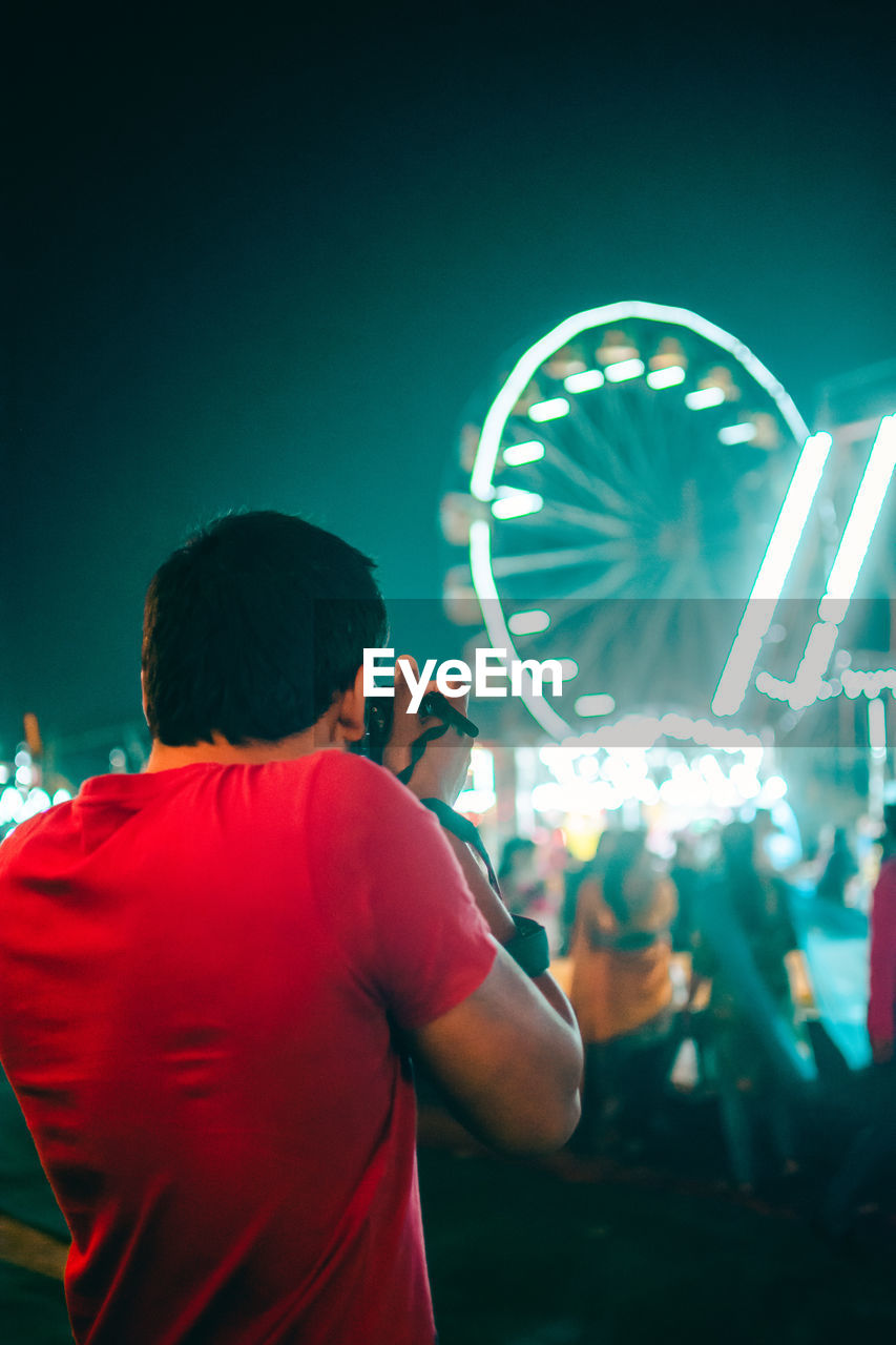 arts culture and entertainment, night, illuminated, rear view, amusement park, real people, men, ferris wheel, leisure activity, amusement park ride, lifestyles, people, standing, motion, casual clothing, waist up, event, adult, performance, nightlife