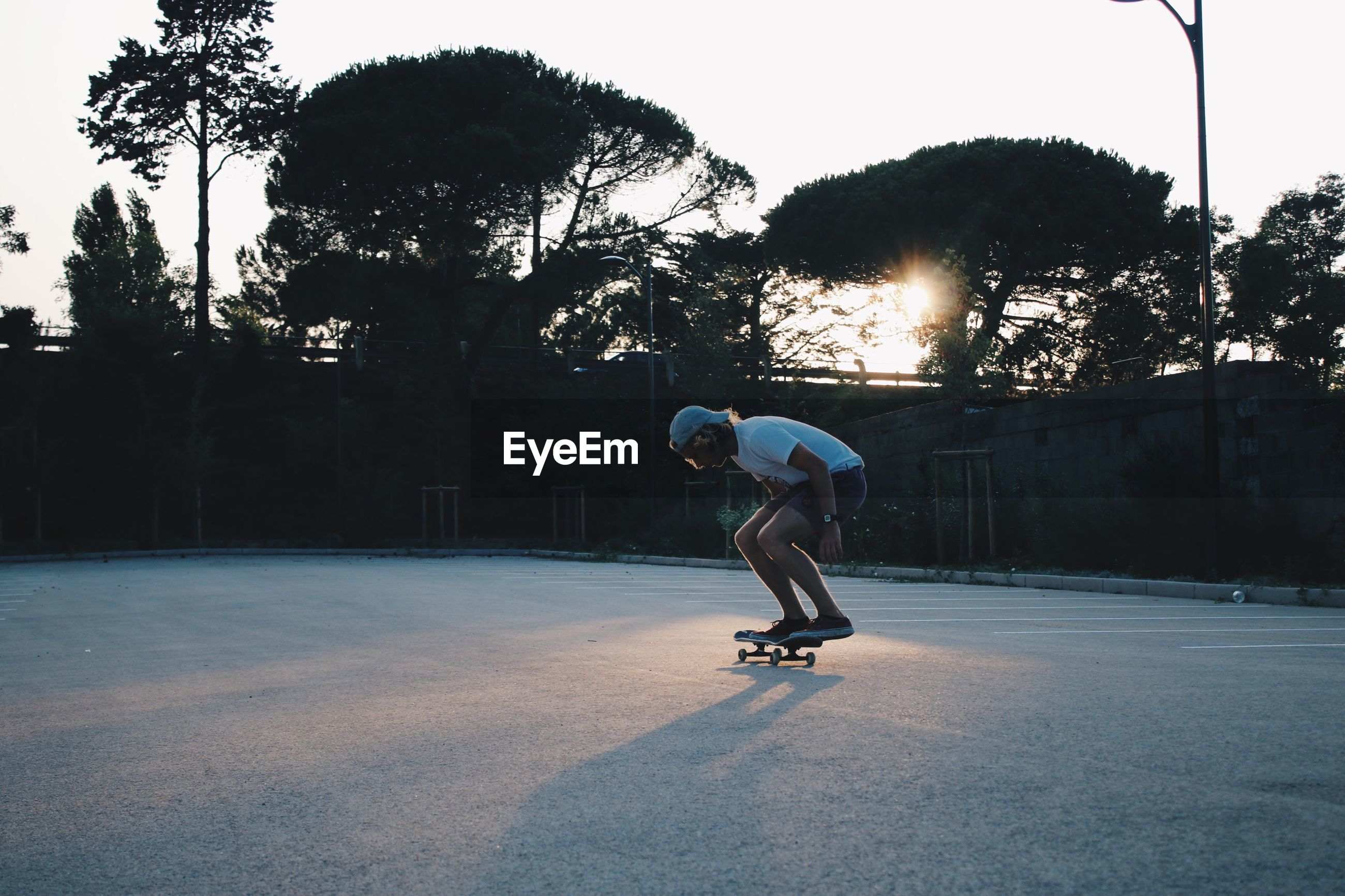 Full length of man skateboarding at playground during sunset