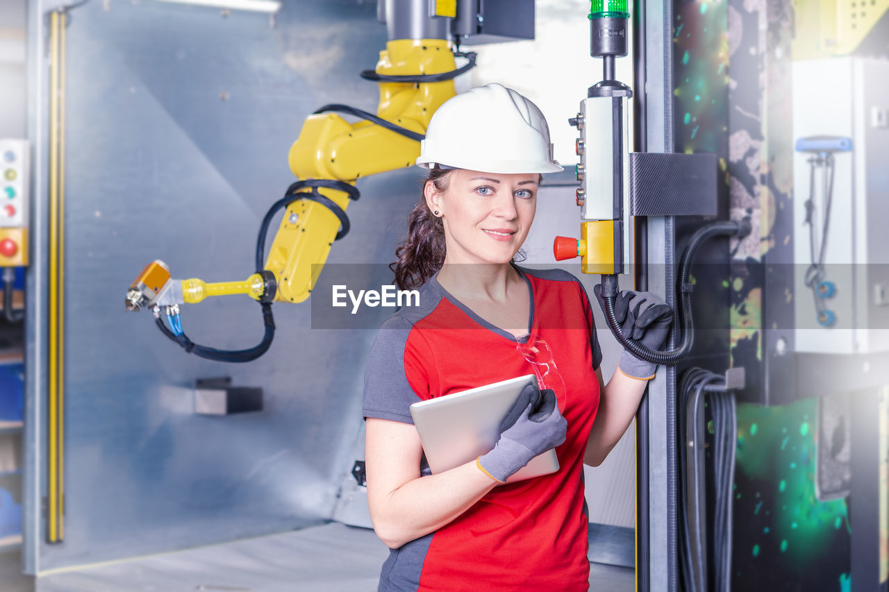 Portrait Of Smiling Technician Standing By Machinery In Factory