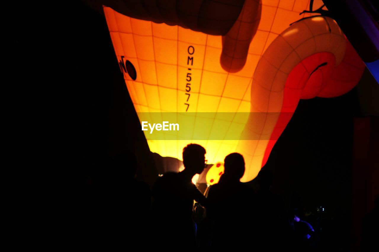 group of people, real people, silhouette, men, illuminated, night, leisure activity, lifestyles, people, arts culture and entertainment, event, orange color, indoors, women, standing, enjoyment, lighting equipment, multi colored, balloon, light, dark, nightlife, paper lantern, festival