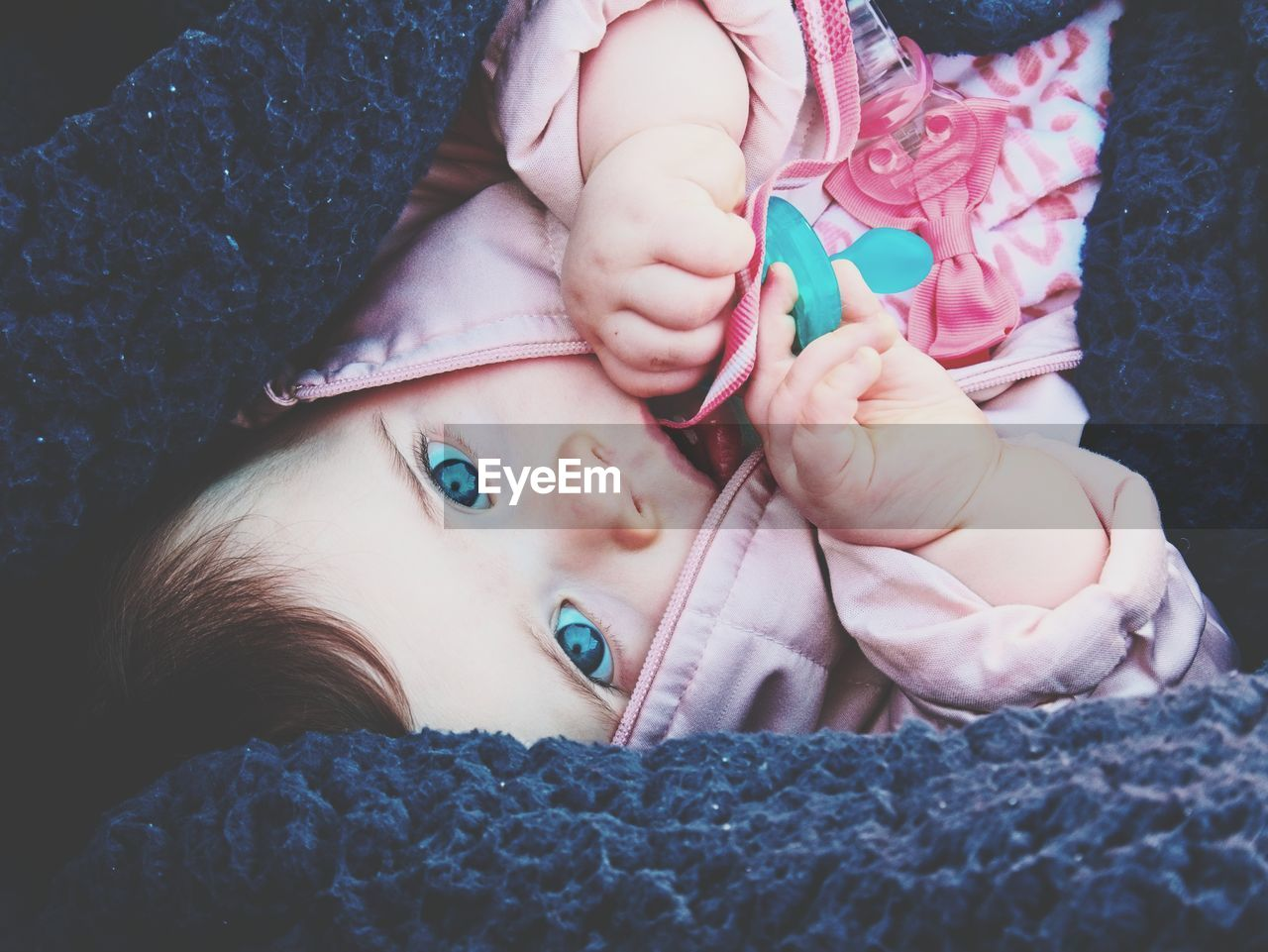 High angle portrait of cute baby girl lying down on bed