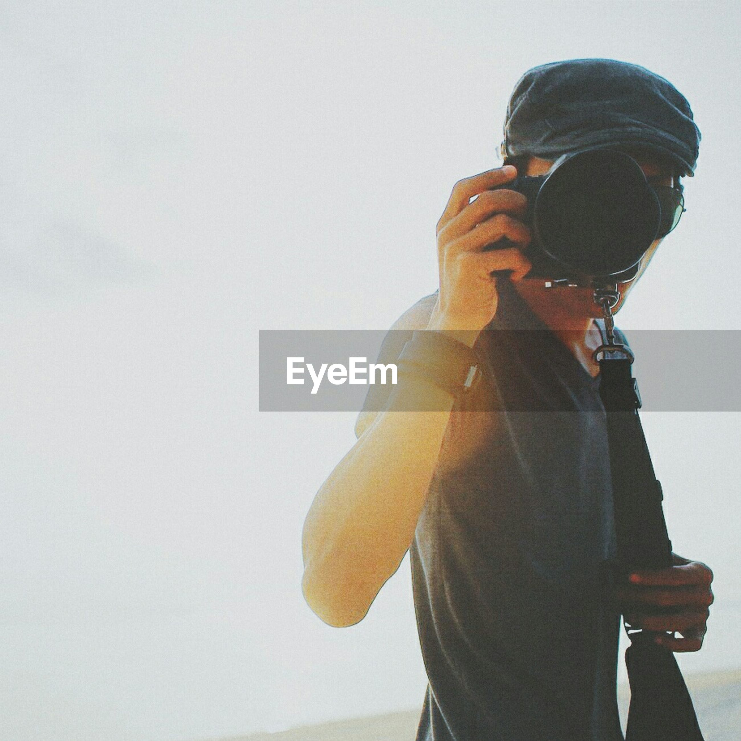 lifestyles, copy space, leisure activity, standing, three quarter length, casual clothing, waist up, rear view, clear sky, men, young adult, young men, holding, low angle view, headshot, side view, sky, hat