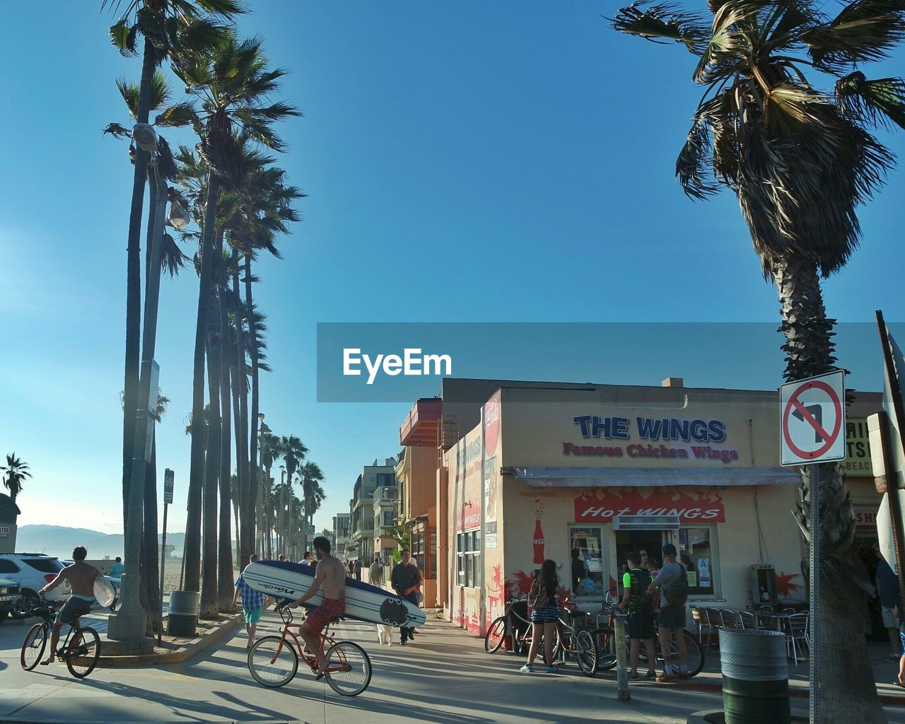 bicycle, day, built structure, real people, architecture, transportation, outdoors, building exterior, tree, men, palm tree, sky, women, city, clear sky, road sign, nature, mammal, people