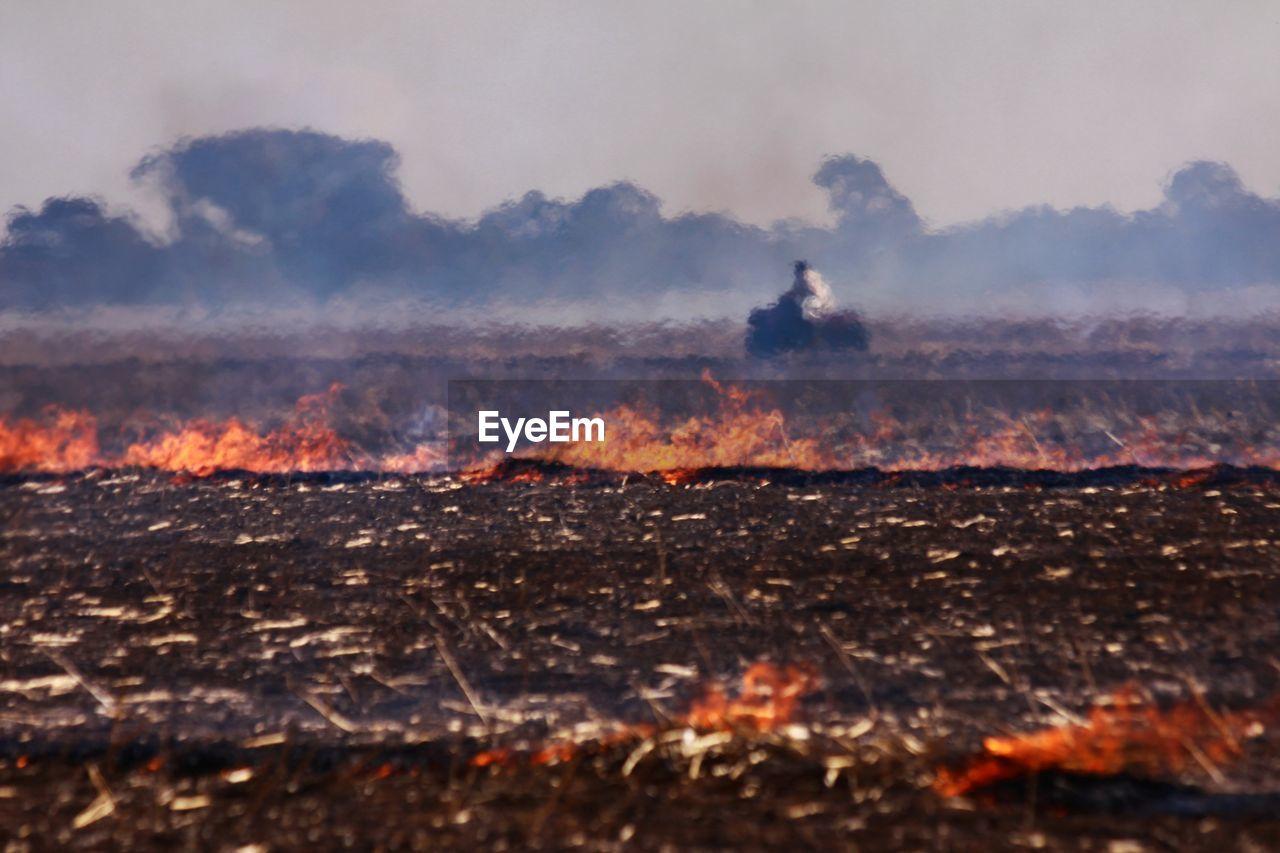 Defocused man riding motorcycle against burning field