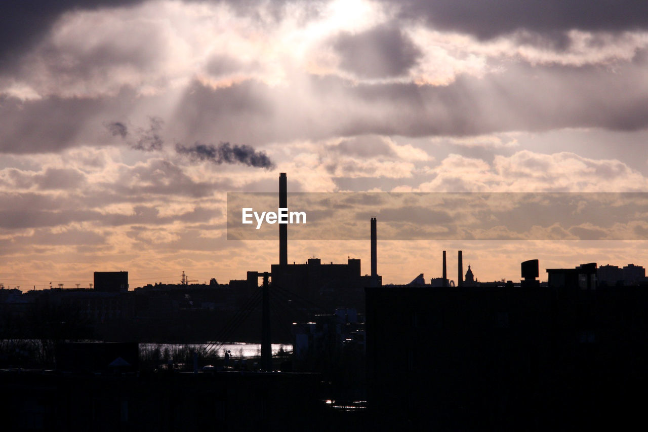 cloud - sky, building exterior, sky, architecture, sunset, built structure, factory, industry, smoke stack, silhouette, no people, city, nature, pollution, smoke - physical structure, environmental issues, outdoors, building, cityscape, sunlight, air pollution, atmospheric