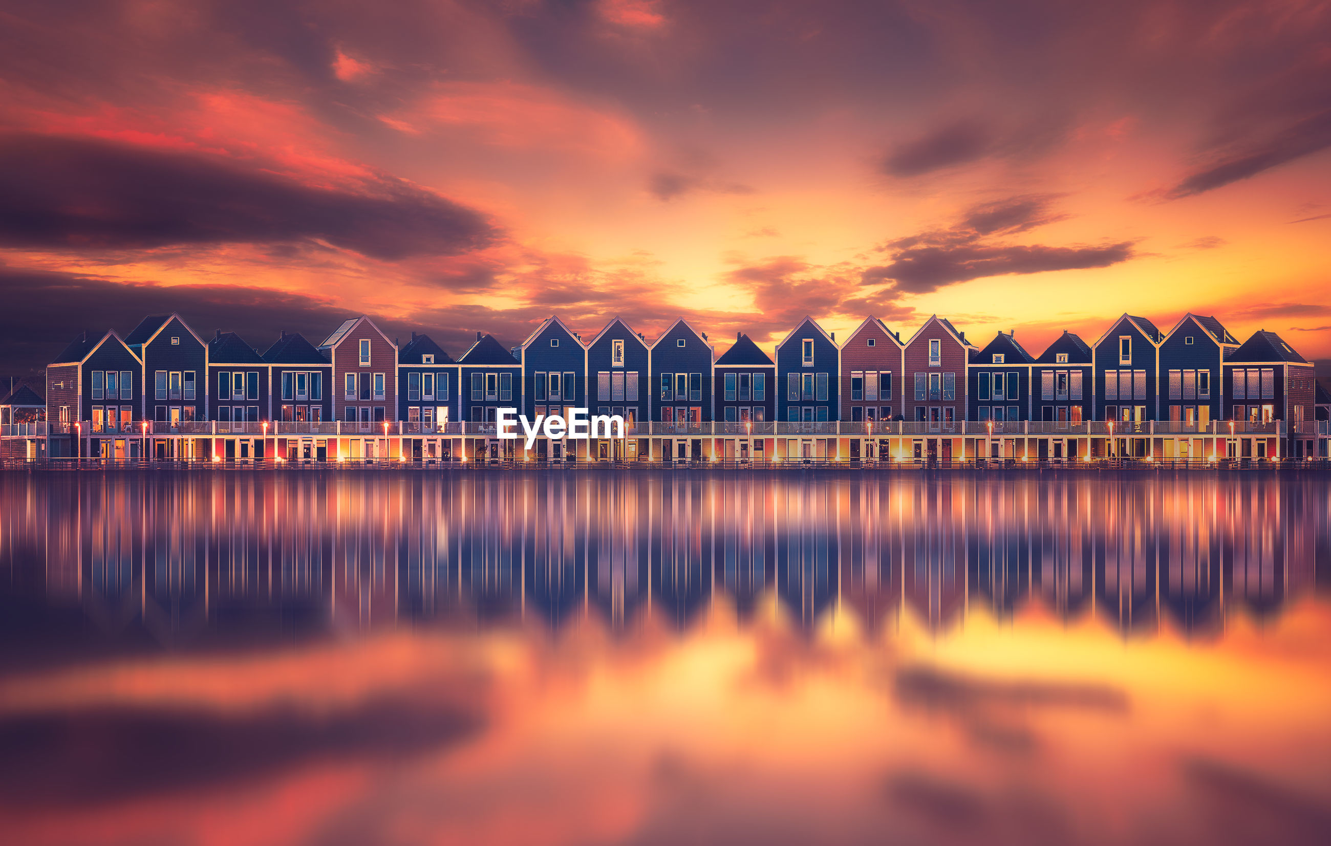 Buildings reflecting on calm lake during sunset in city
