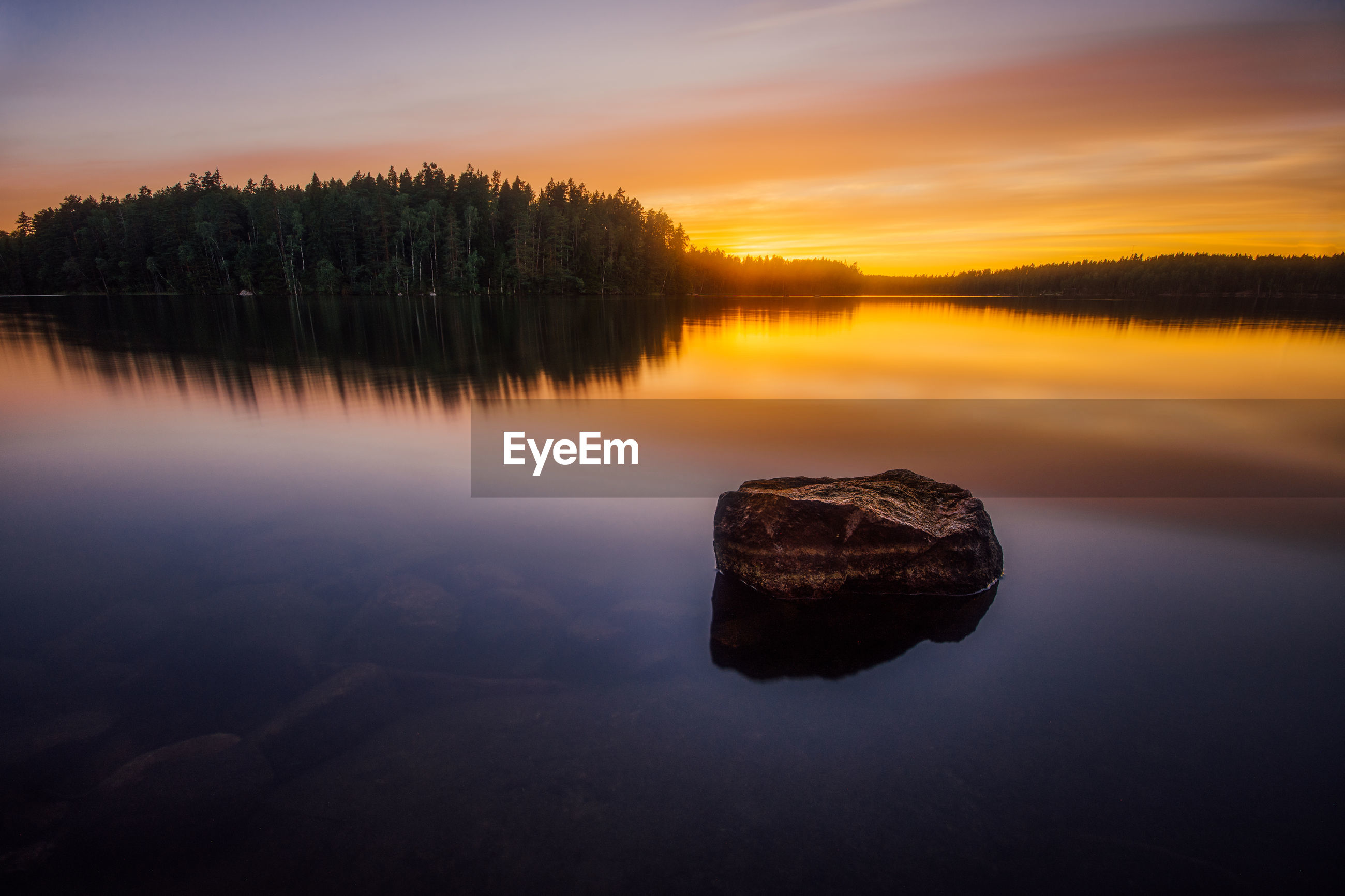Scenic view of lake with rock and trees reflection at sunset