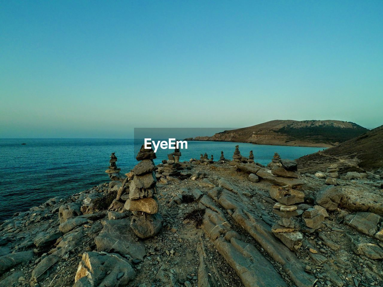 sea, water, sky, clear sky, copy space, scenics - nature, horizon, nature, land, rock, beauty in nature, horizon over water, beach, tranquil scene, tranquility, non-urban scene, blue, outdoors, rock - object