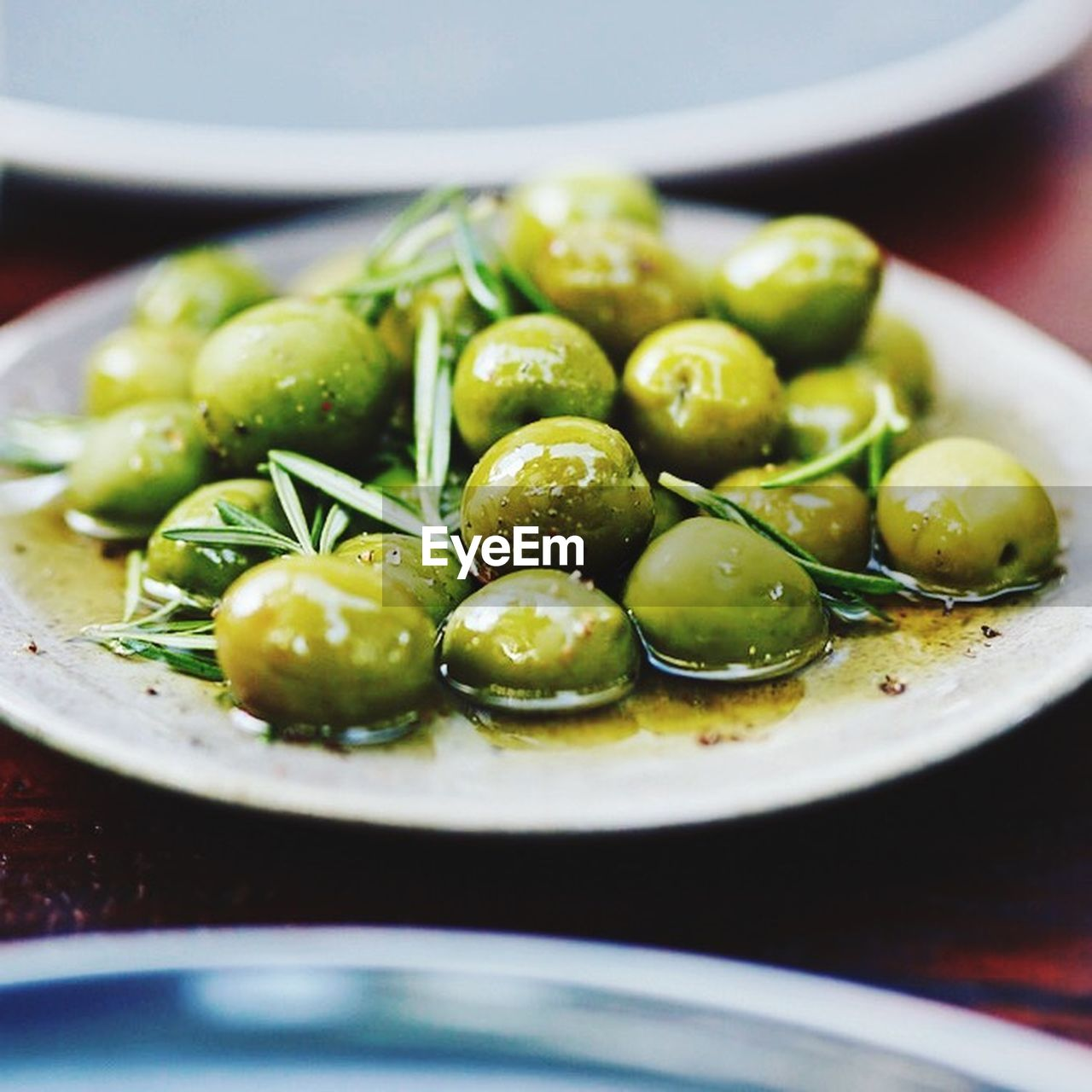 food, food and drink, healthy eating, freshness, close-up, wellbeing, indoors, olive, no people, plate, fruit, green color, still life, bowl, kitchen utensil, selective focus, green olive, focus on foreground, table, abundance