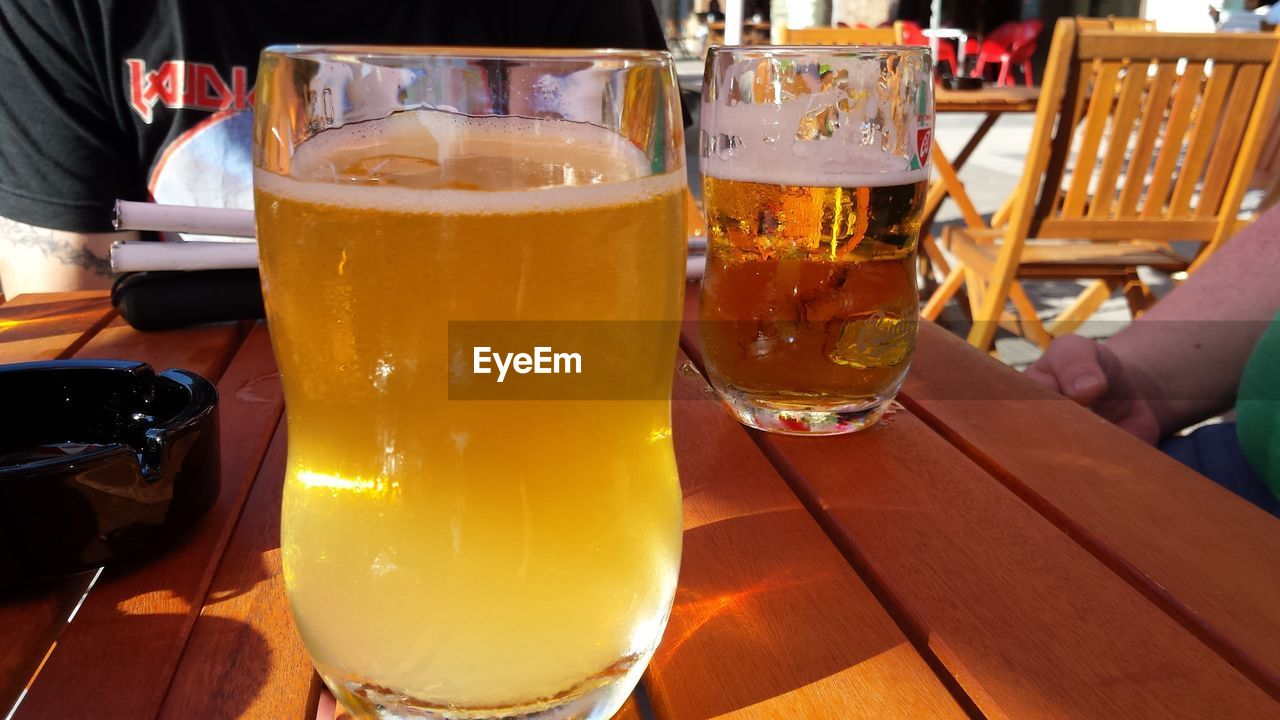 beer glass, drink, beer - alcohol, alcohol, beer, table, drinking glass, human hand, food and drink, refreshment, human body part, real people, frothy drink, alcoholic drink, freshness, pint glass, froth, close-up, indoors, day, men, happy hour, one person, people