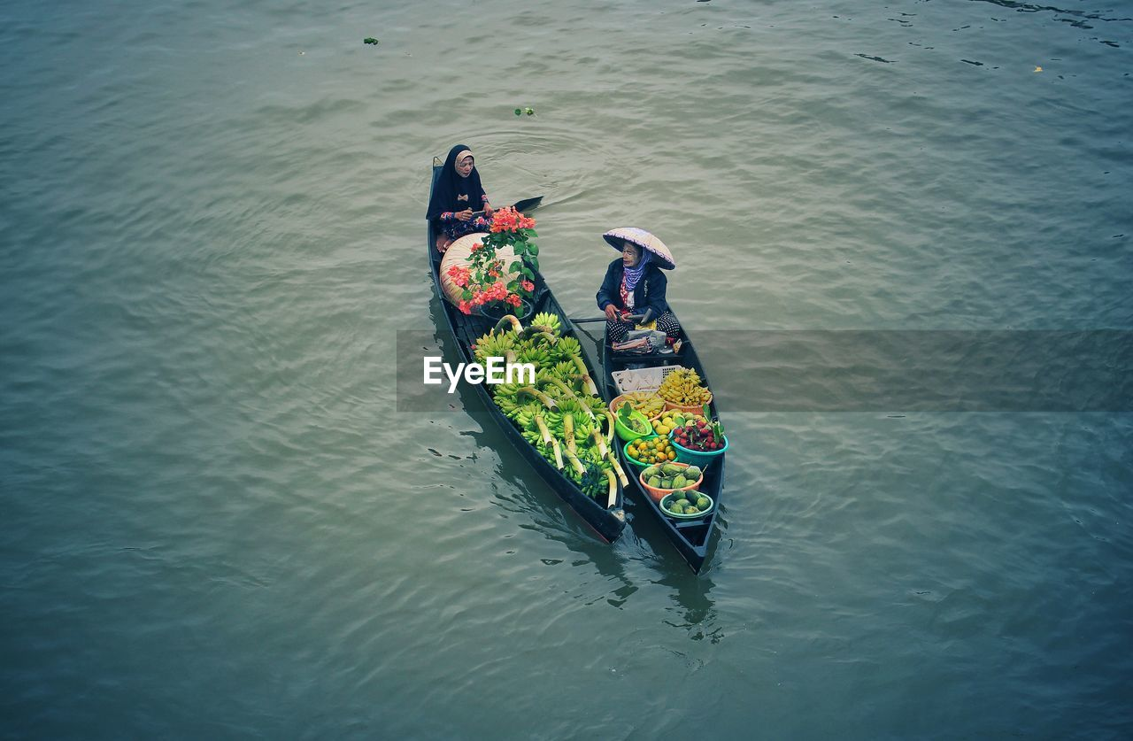 water, nautical vessel, waterfront, real people, transportation, mode of transportation, high angle view, lifestyles, men, people, leisure activity, day, river, nature, outdoors, adult, women