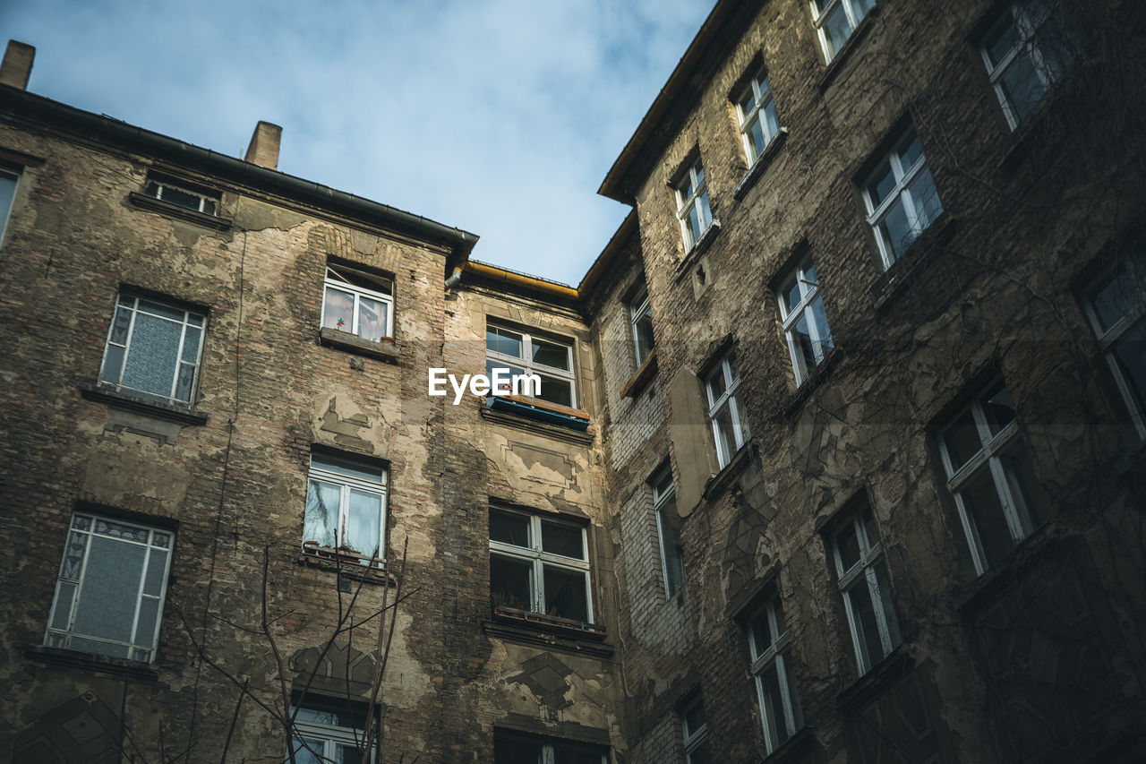building exterior, built structure, window, low angle view, architecture, building, sky, residential district, no people, cloud - sky, nature, day, outdoors, city, old, wall, glass - material, in a row, side by side, house, apartment