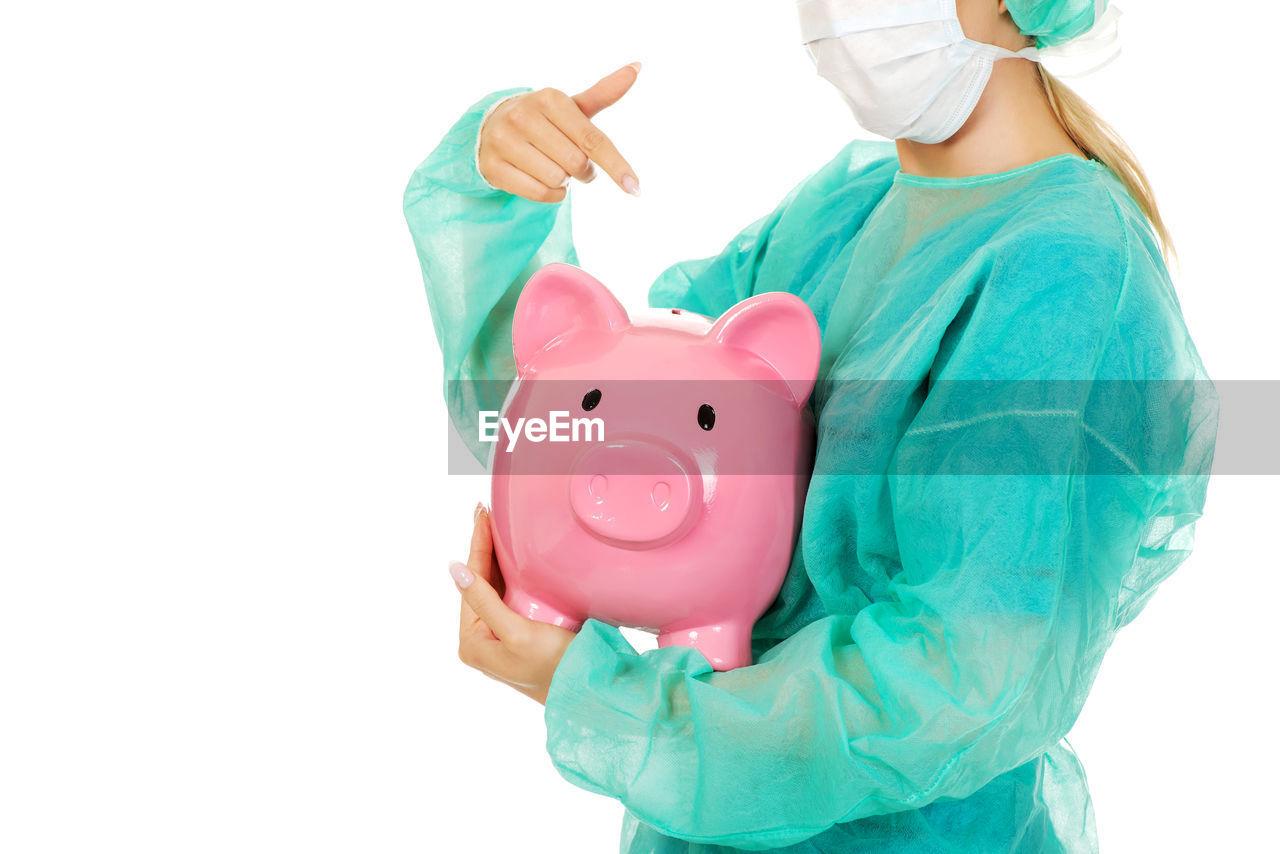 Female Doctor Holding Piggy Bank Against White Background