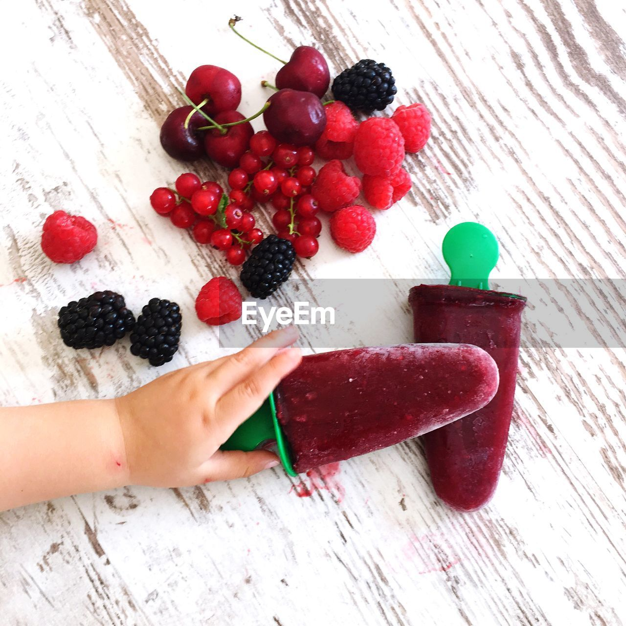 food, food and drink, berry fruit, healthy eating, human hand, fruit, wellbeing, red, freshness, high angle view, one person, human body part, table, indoors, hand, real people, holding, finger, wood - material, human finger, temptation