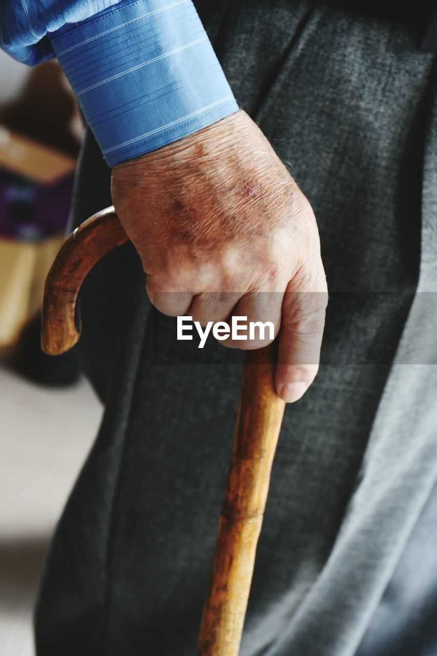 Midsection Of A Senior Man Holding Walking Cane