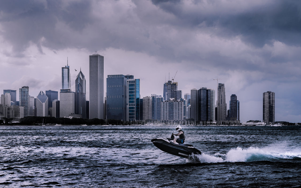 building exterior, architecture, built structure, sky, water, city, cloud - sky, office building exterior, nautical vessel, building, urban skyline, waterfront, skyscraper, transportation, sea, tall - high, nature, cityscape, motion, outdoors, modern, financial district