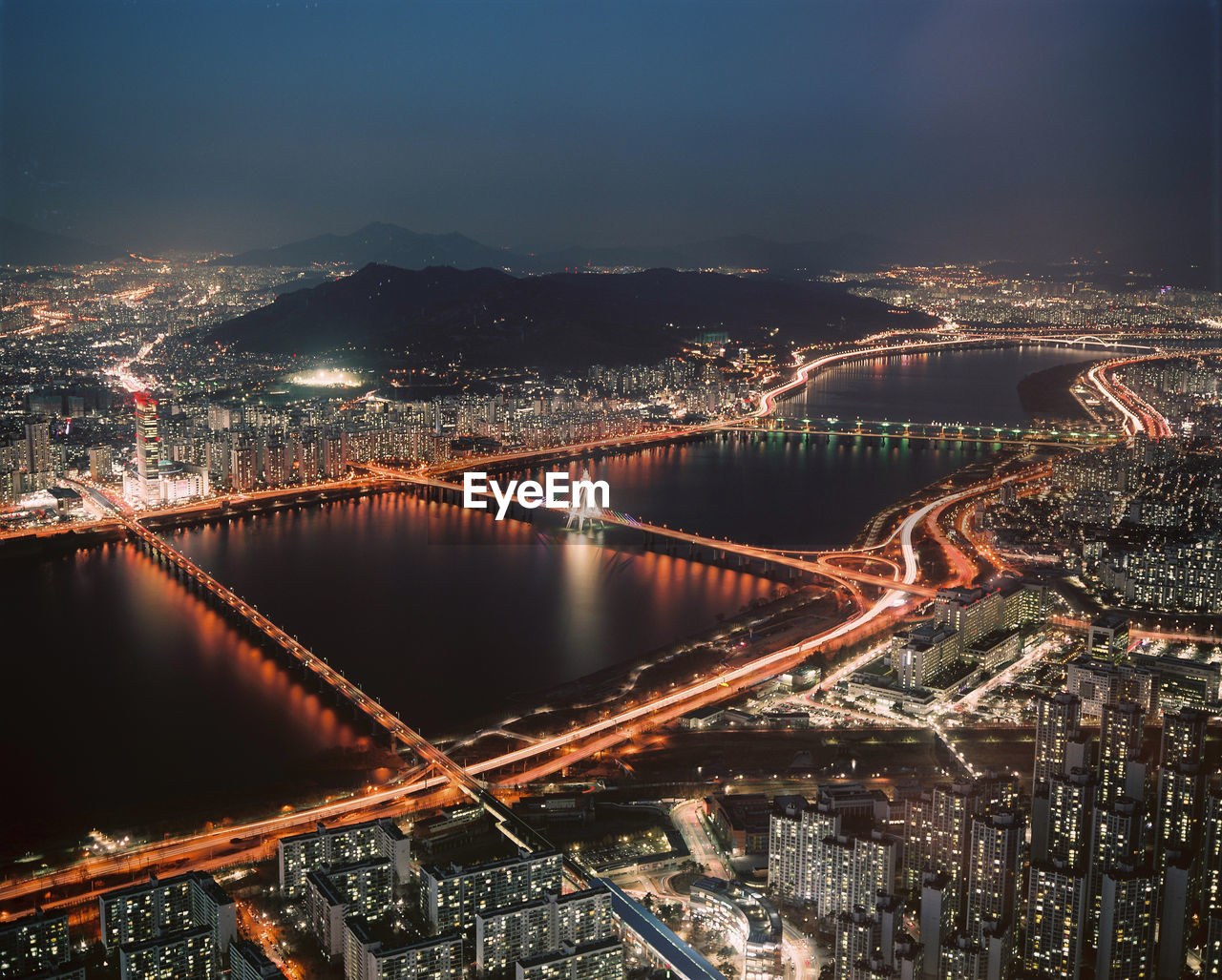 High angle view of city and suspension bridge at night