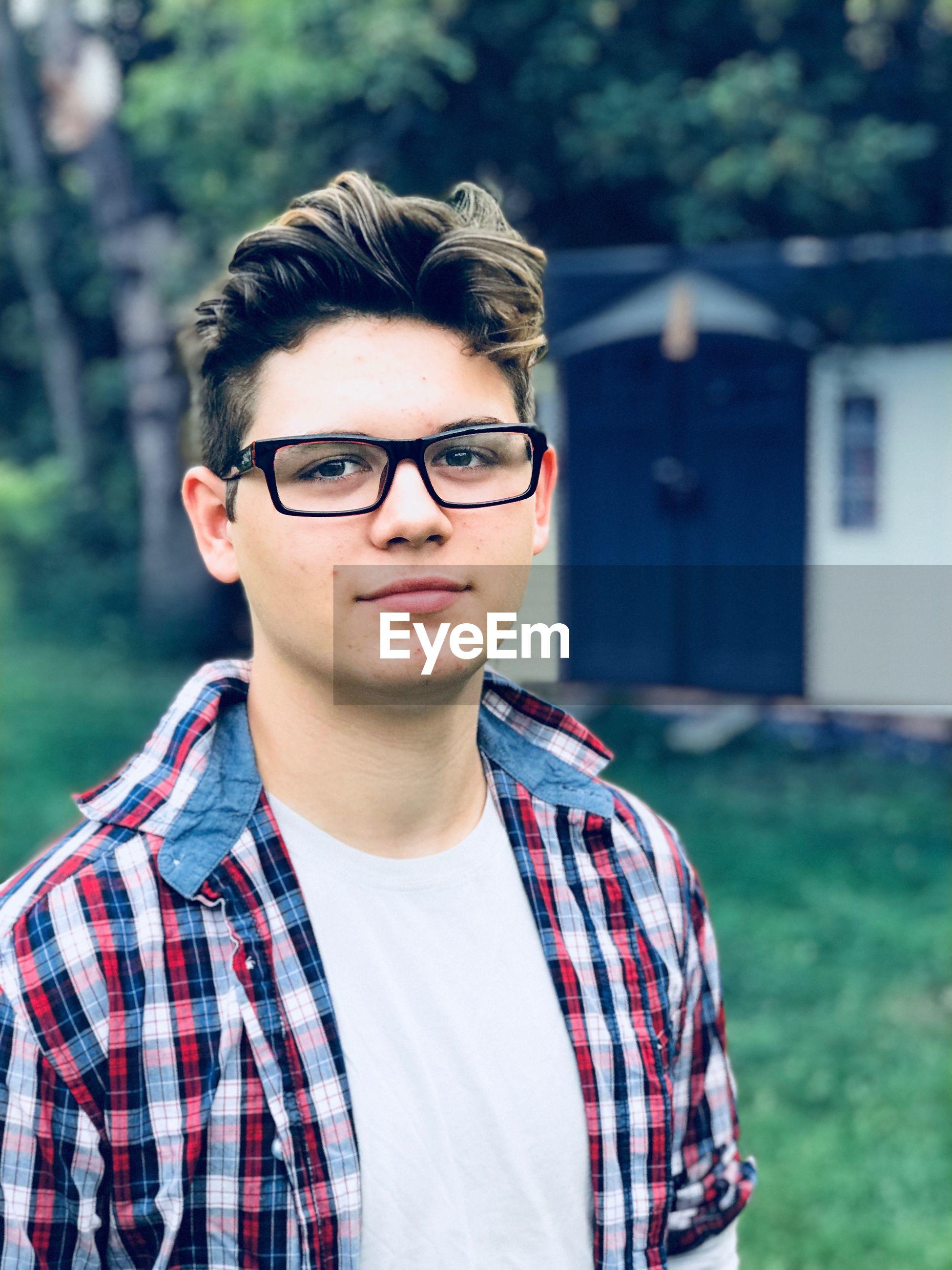 Portrait of teenage boy wearing eyeglasses outdoors