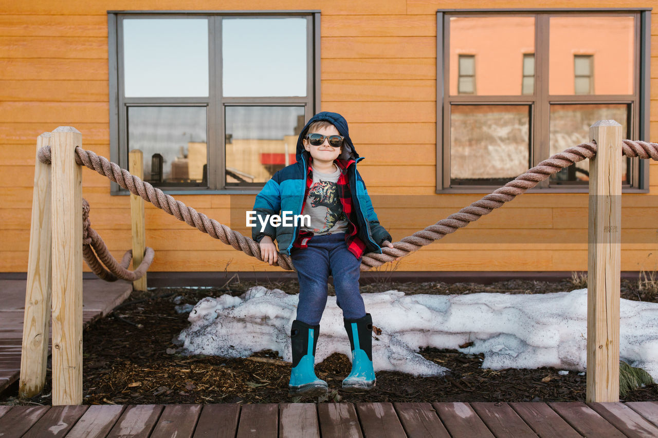Portrait of boy in sunglasses sitting on rope