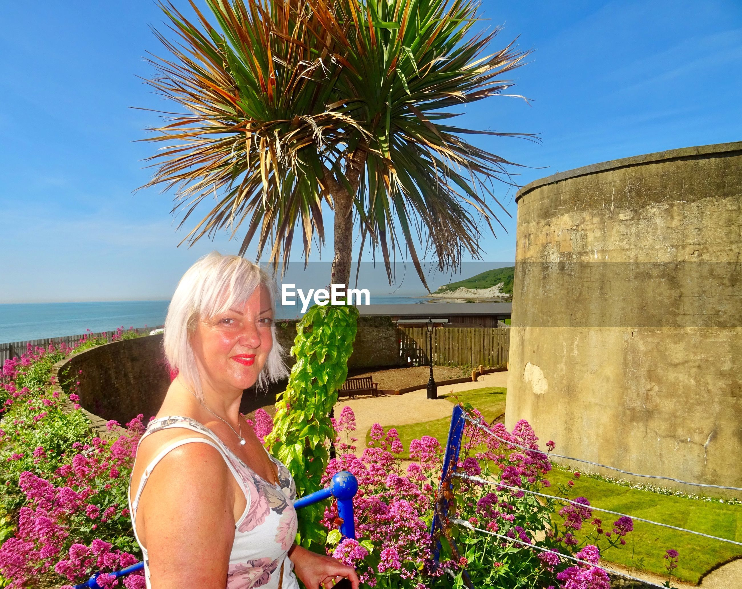 Portrait of smiling mature woman standing by plants against blue sky during sunny day