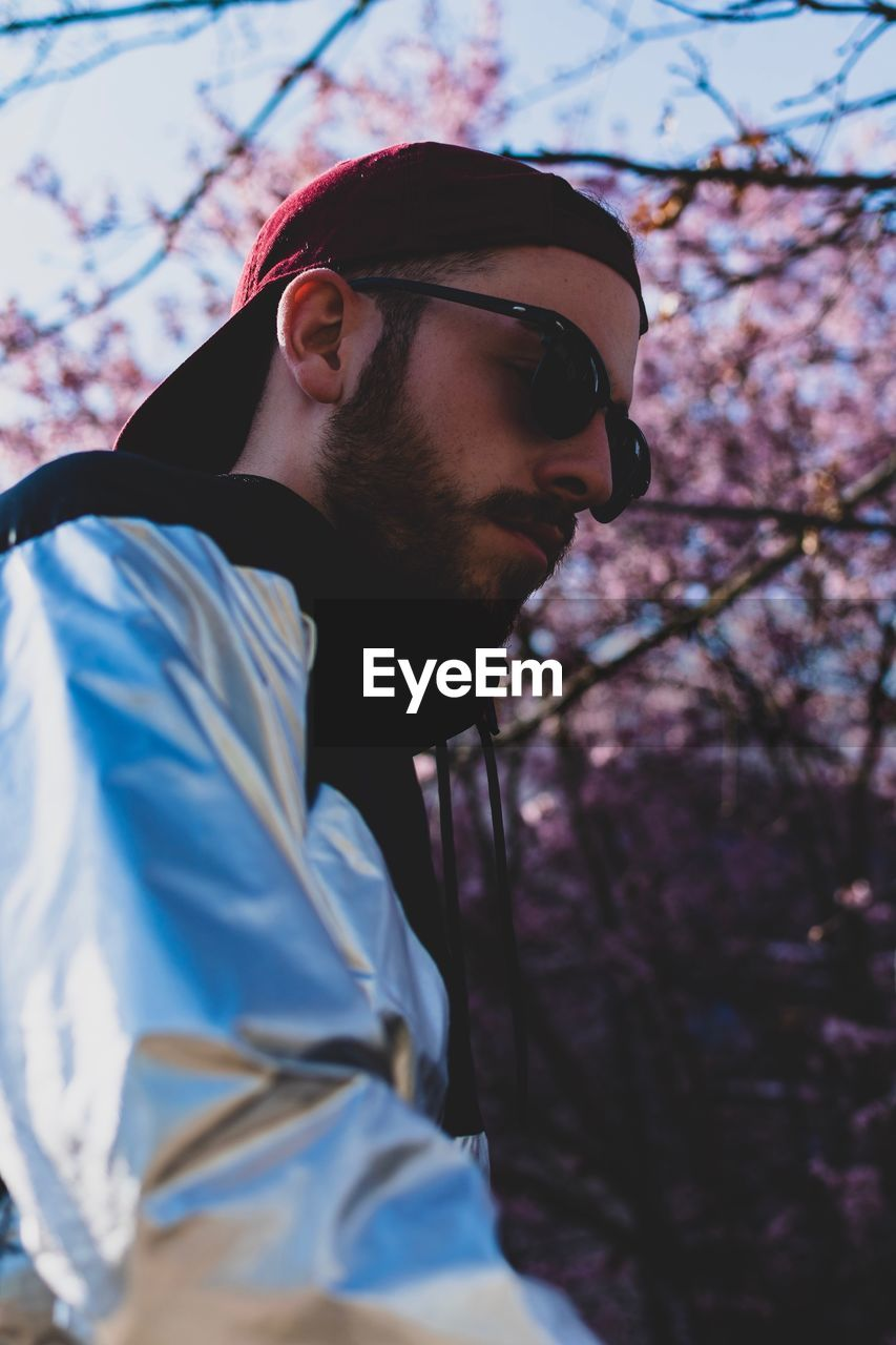 one person, glasses, young men, real people, tree, plant, young adult, leisure activity, lifestyles, focus on foreground, sunglasses, men, nature, beard, fashion, looking away, casual clothing, facial hair, looking, outdoors, contemplation