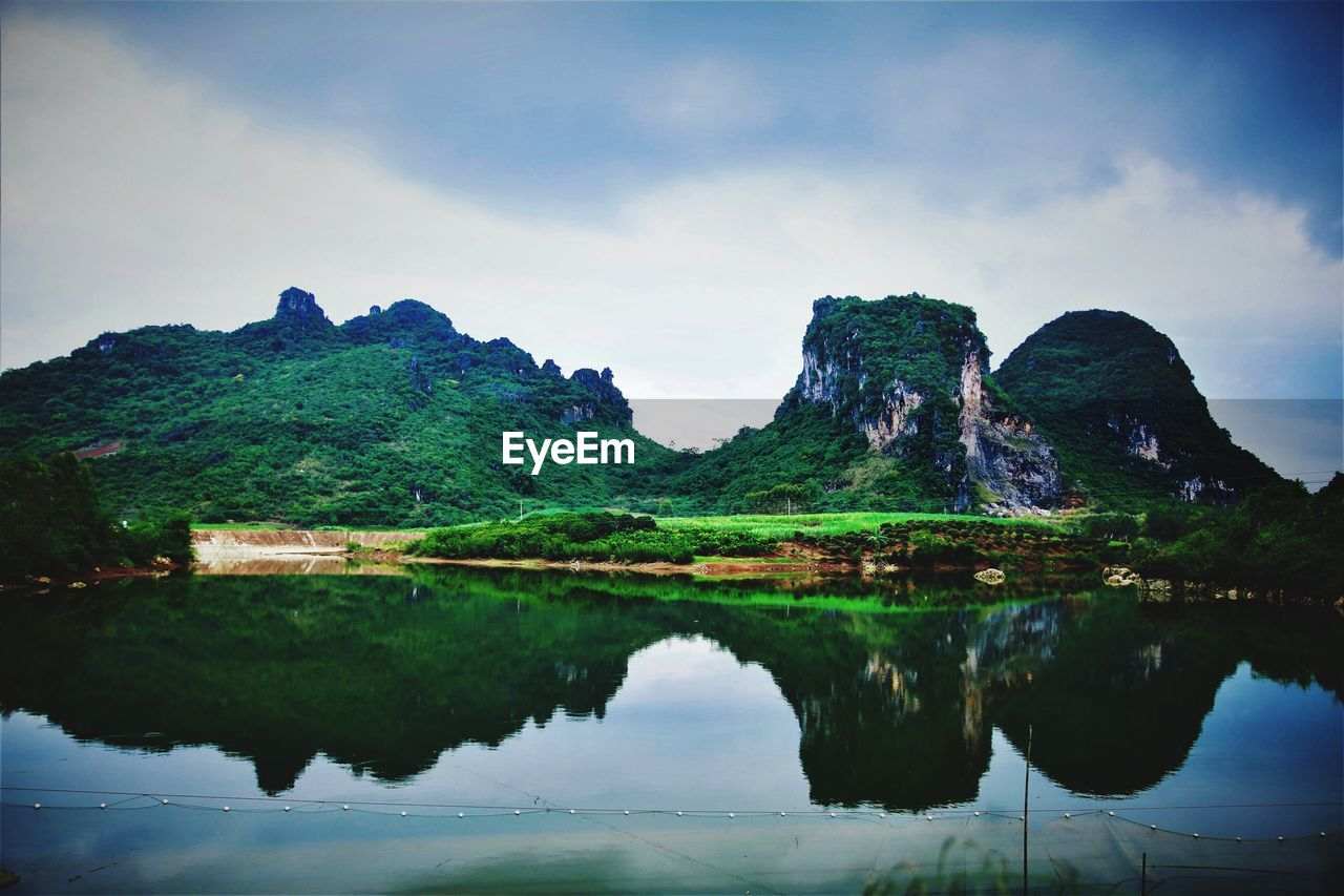 Mountains By Lake Against Cloudy Sky