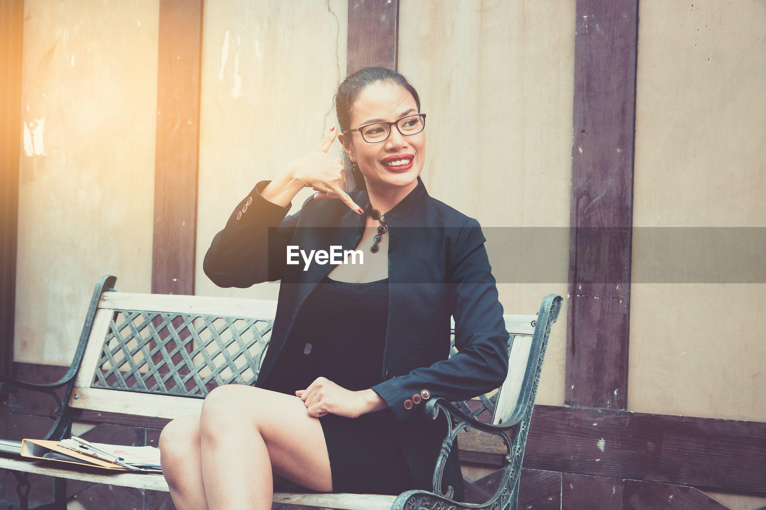 Smiling woman gesturing while sitting on bench at footpath