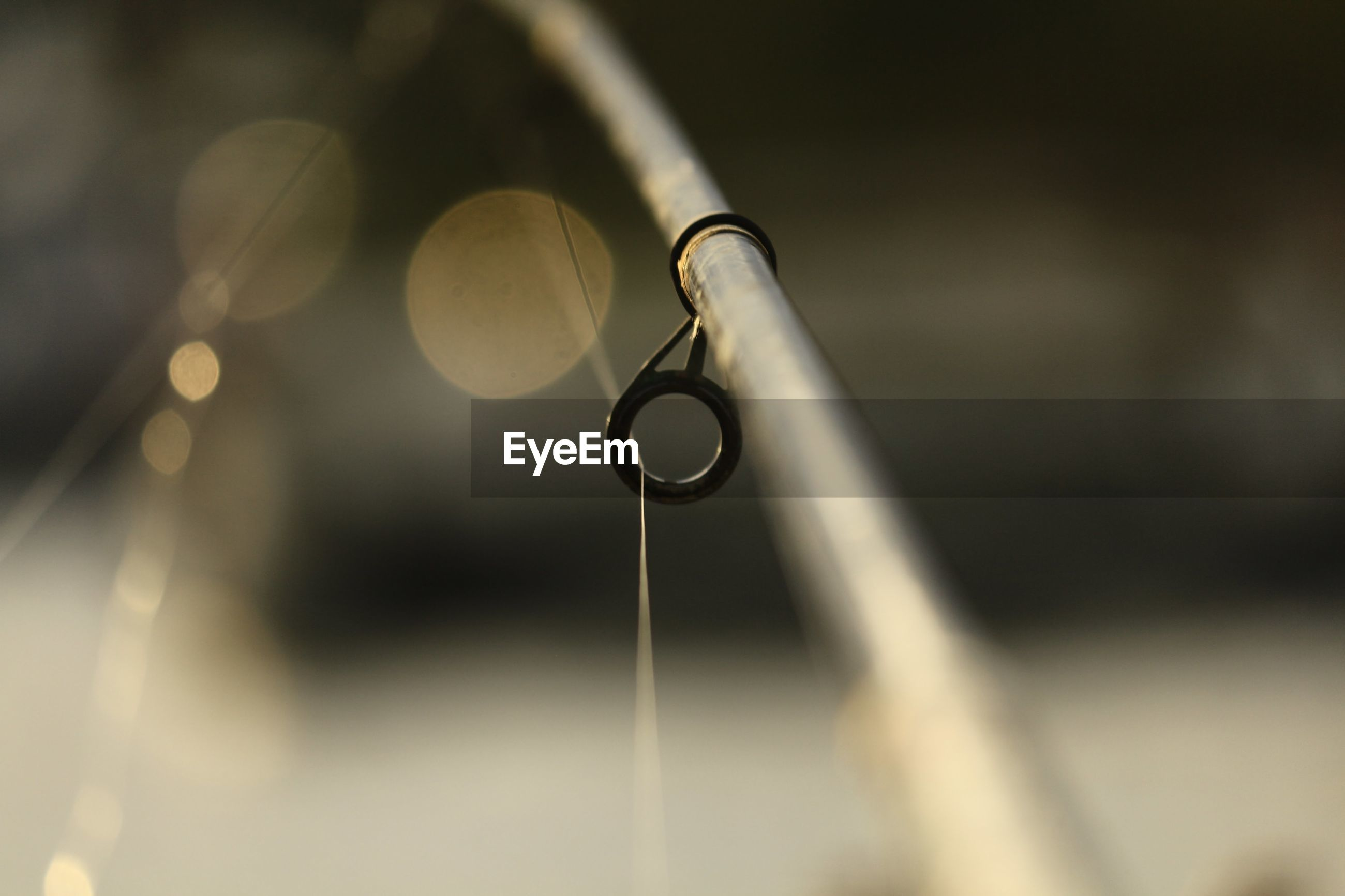 CLOSE-UP OF WATER DROP HANGING FROM METAL