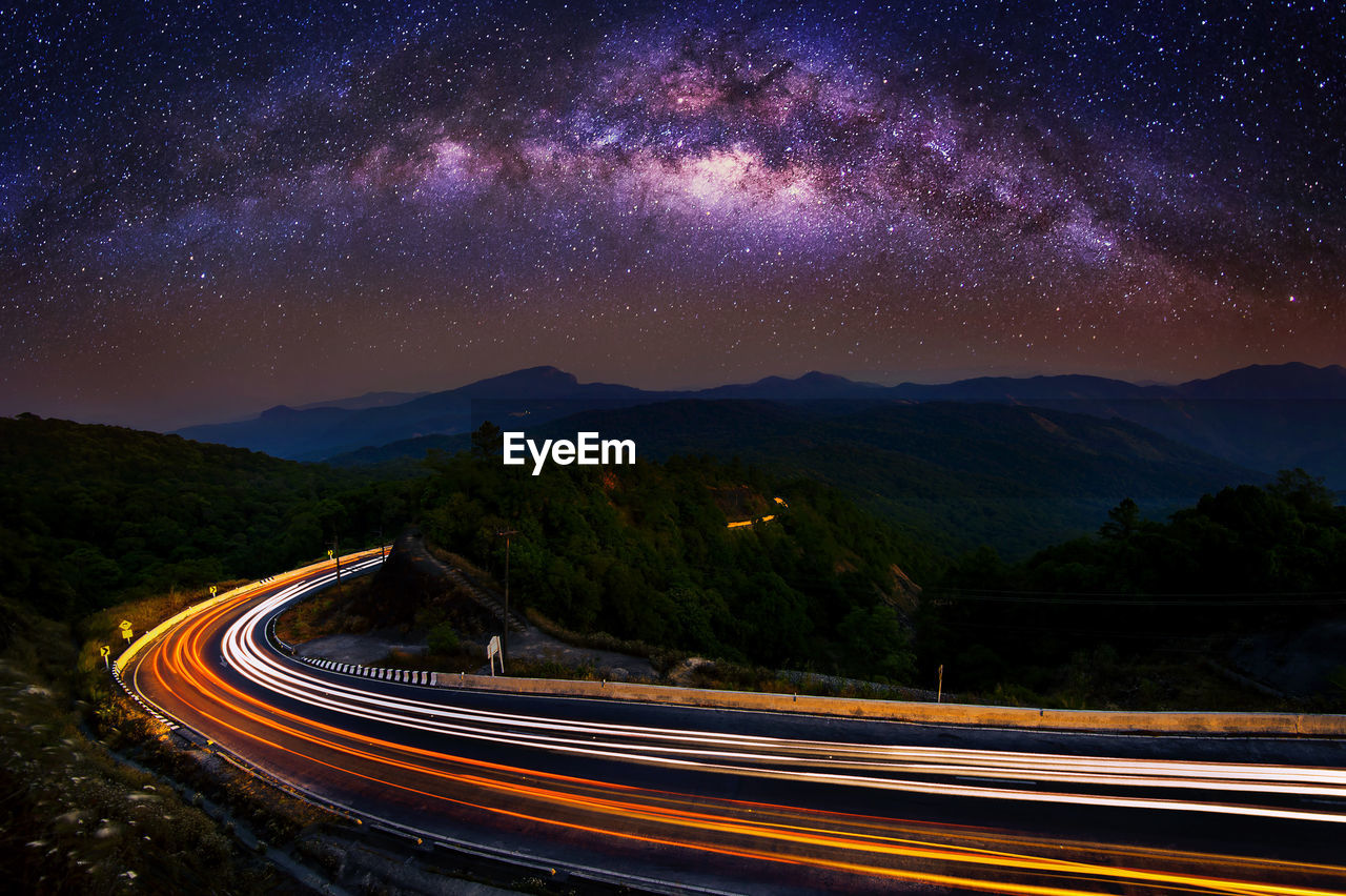 Light Trails On Road By Mountains Against Sky At Night
