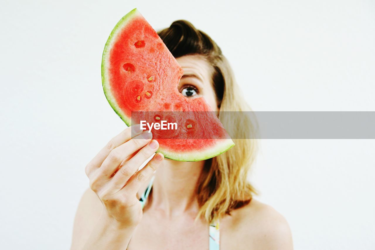 Close-up of woman holding watermelon against white background
