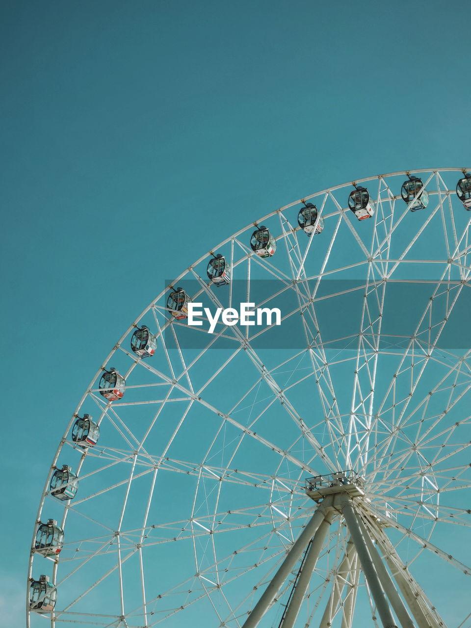 amusement park ride, amusement park, sky, arts culture and entertainment, ferris wheel, low angle view, clear sky, nature, blue, no people, fairground, large, leisure activity, outdoors, geometric shape, circle, day, shape, architecture, built structure, high, spoke
