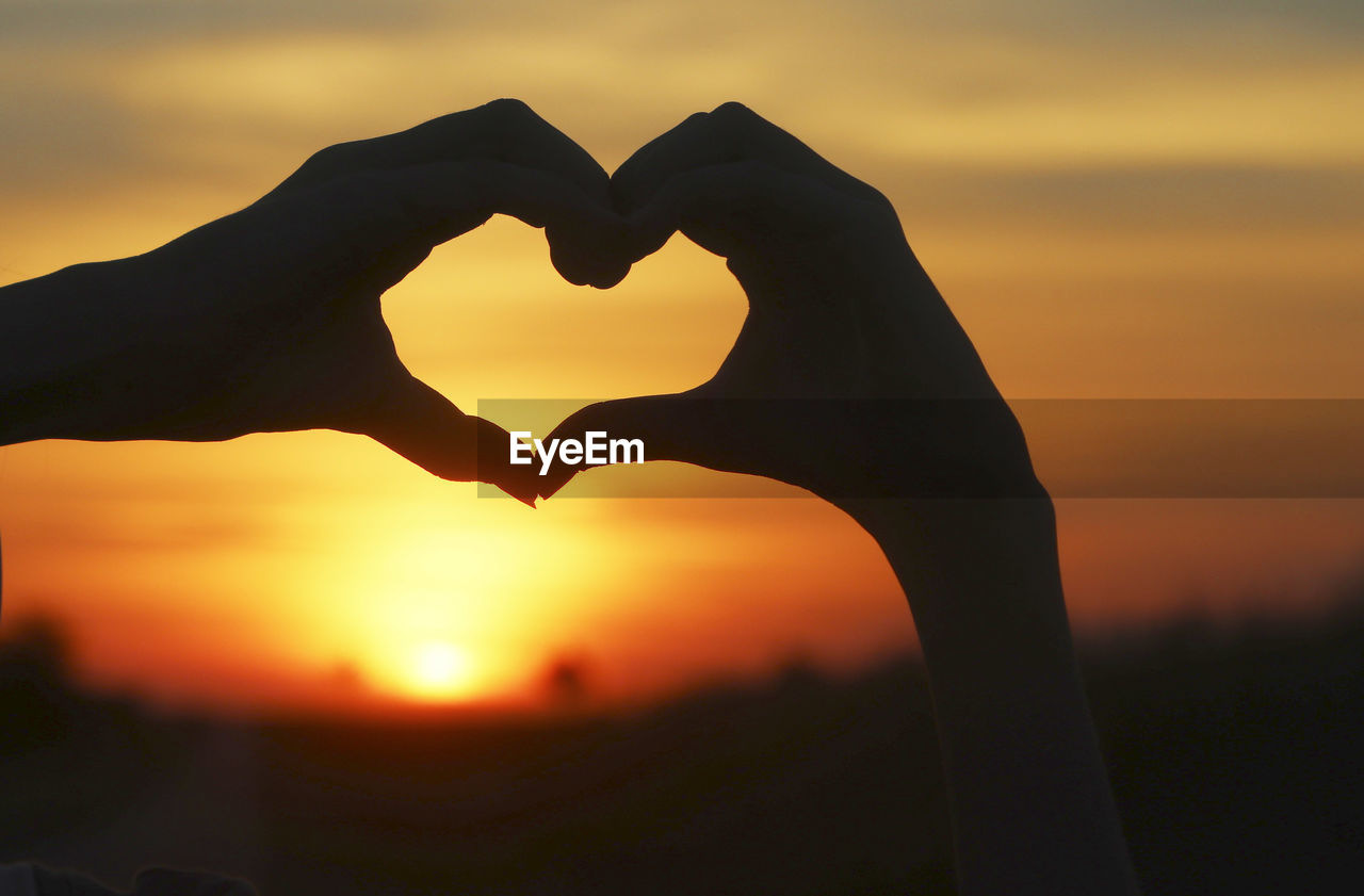 Silhouette of hands making heart shape against sky during sunset