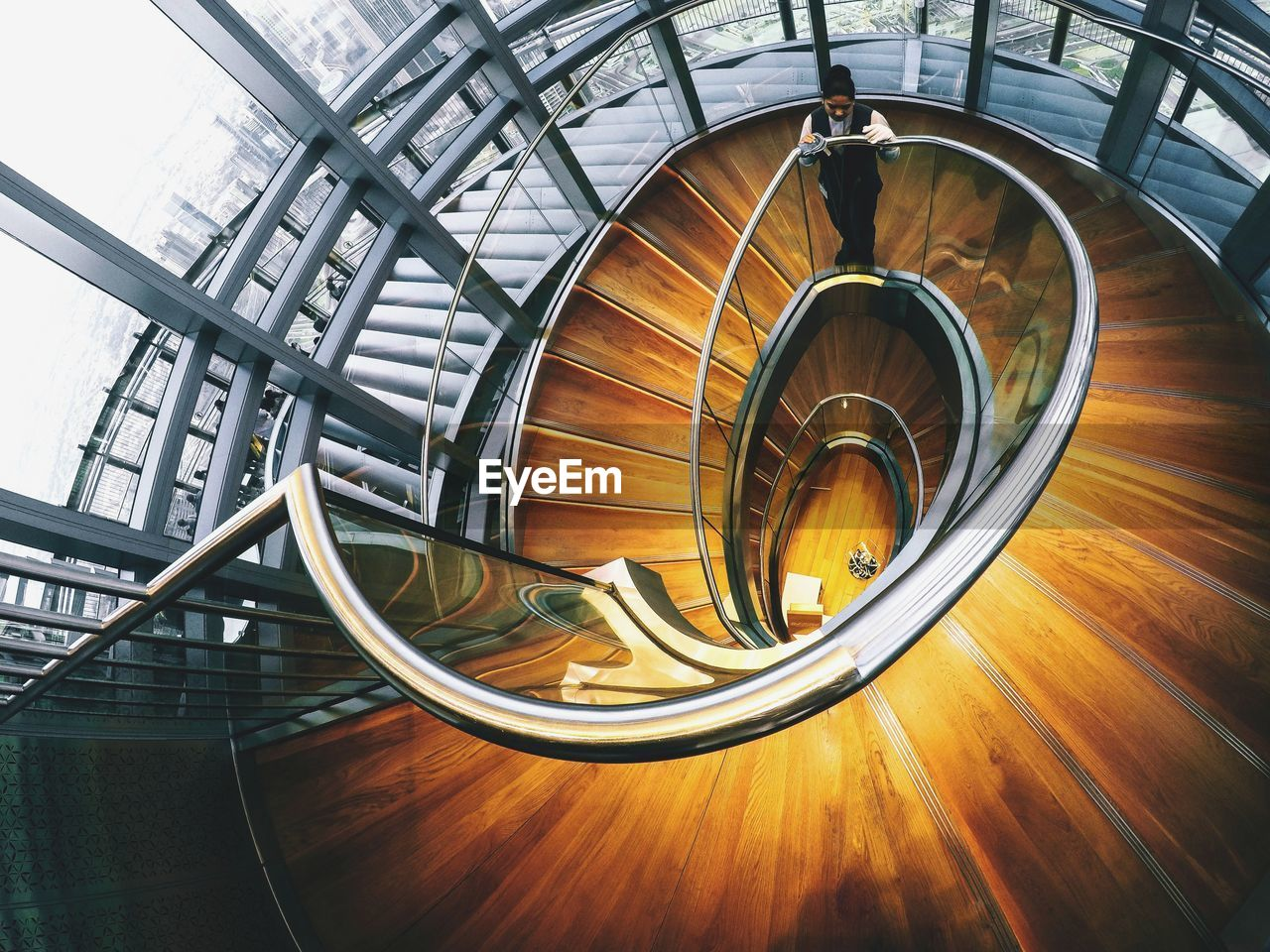 High angle view of woman standing on spiral staircase in building