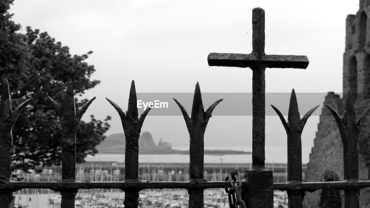 religion, belief, spirituality, cross, focus on foreground, place of worship, architecture, sky, fence, no people, nature, built structure, day, barrier, cross shape, boundary, symbol, metal, outdoors