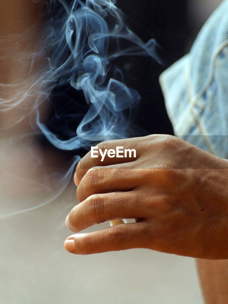 Close-Up Of Human Hand Holding Burning Cigarette Outdoors