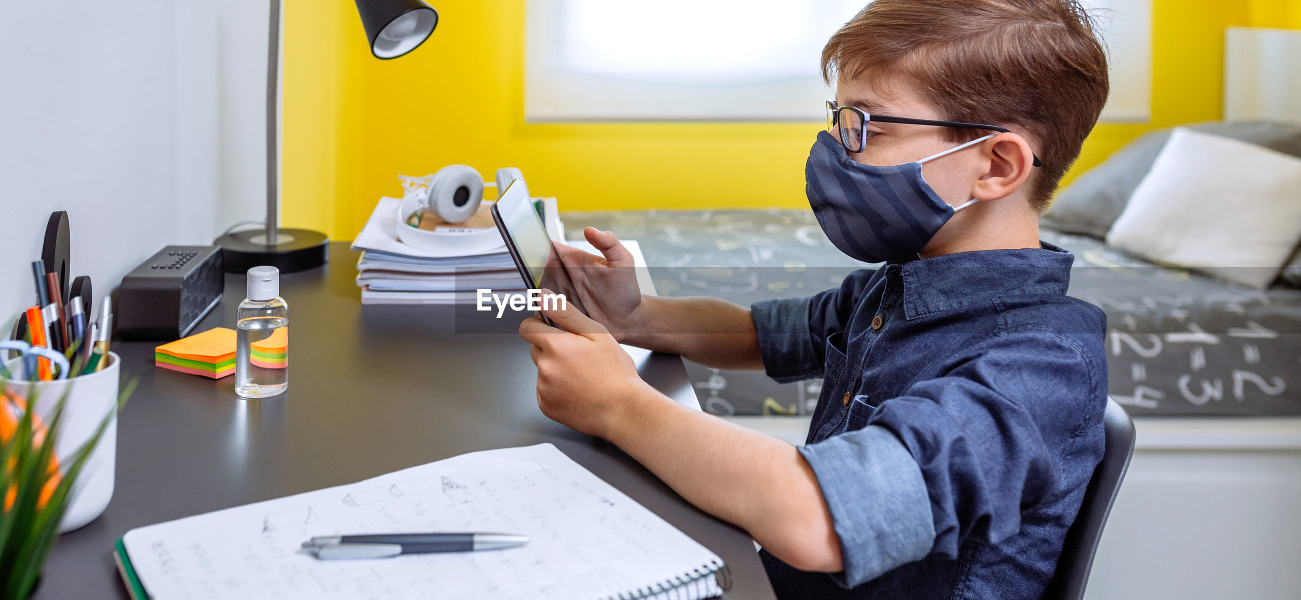 Boy wearing mask studying with digital tablet at home