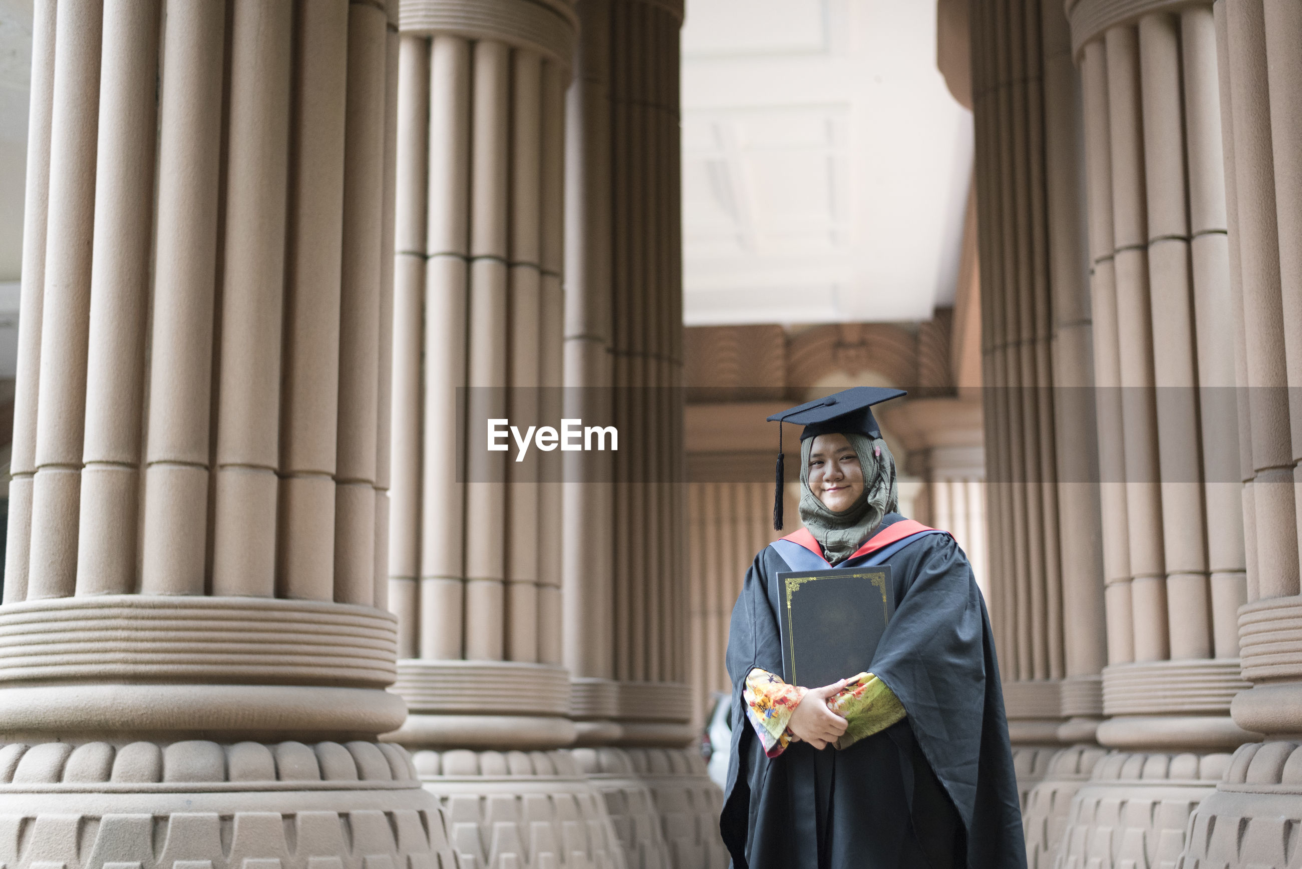 Portrait of smiling young woman wearing graduation gown at university