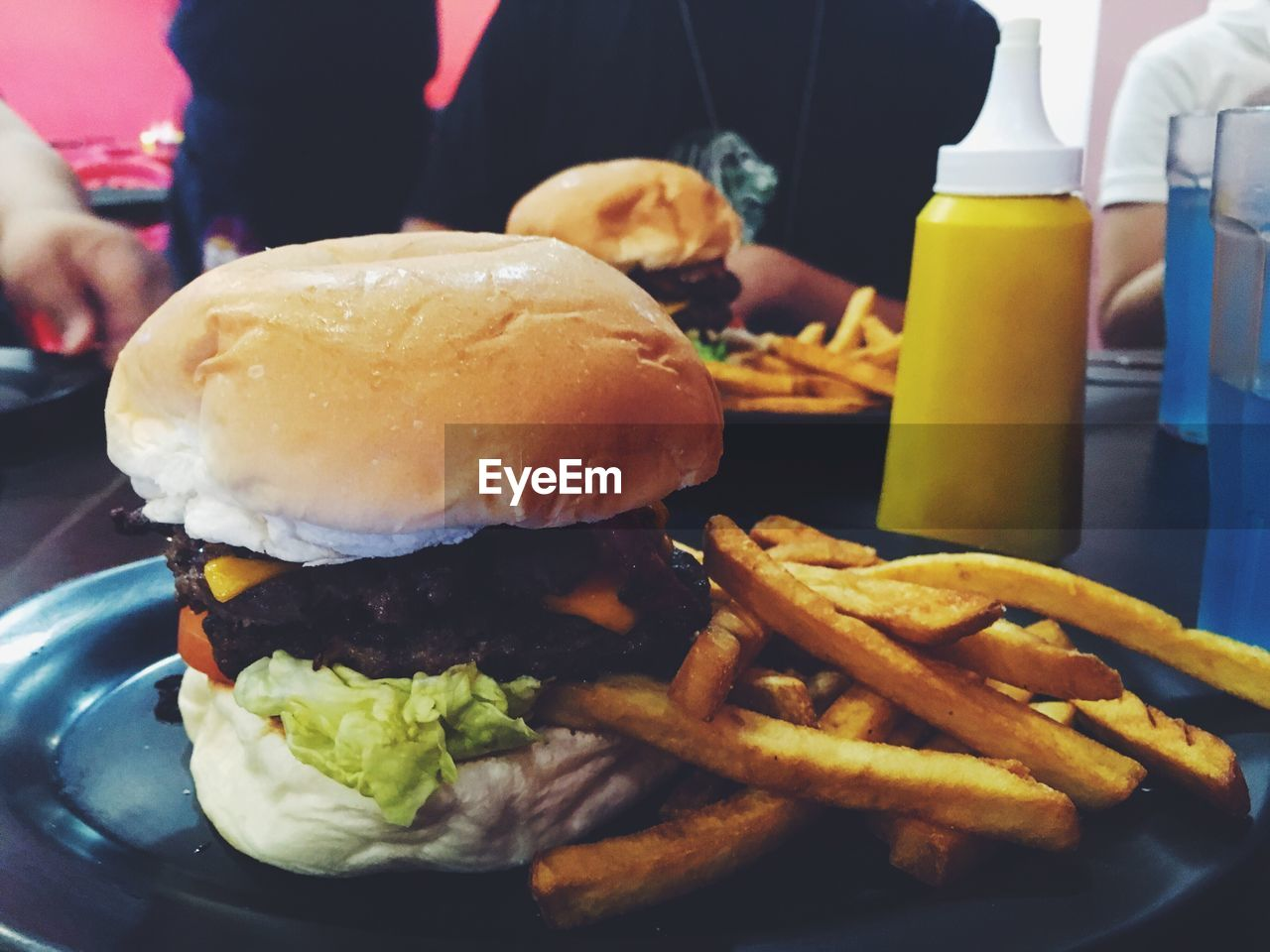 food and drink, french fries, unhealthy eating, food, prepared potato, burger, fast food, hamburger, real people, freshness, indoors, table, ready-to-eat, take out food, deep fried, indulgence, serving size, close-up, men, bun, one person, human hand, day, people