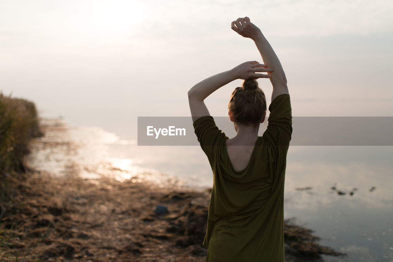 sea, sky, real people, beach, nature, one person, outdoors, focus on foreground, water, women, sunset, beauty in nature, lifestyles, leisure activity, standing, sand, full length, young women, day, scenics, horizon over water, young adult, people