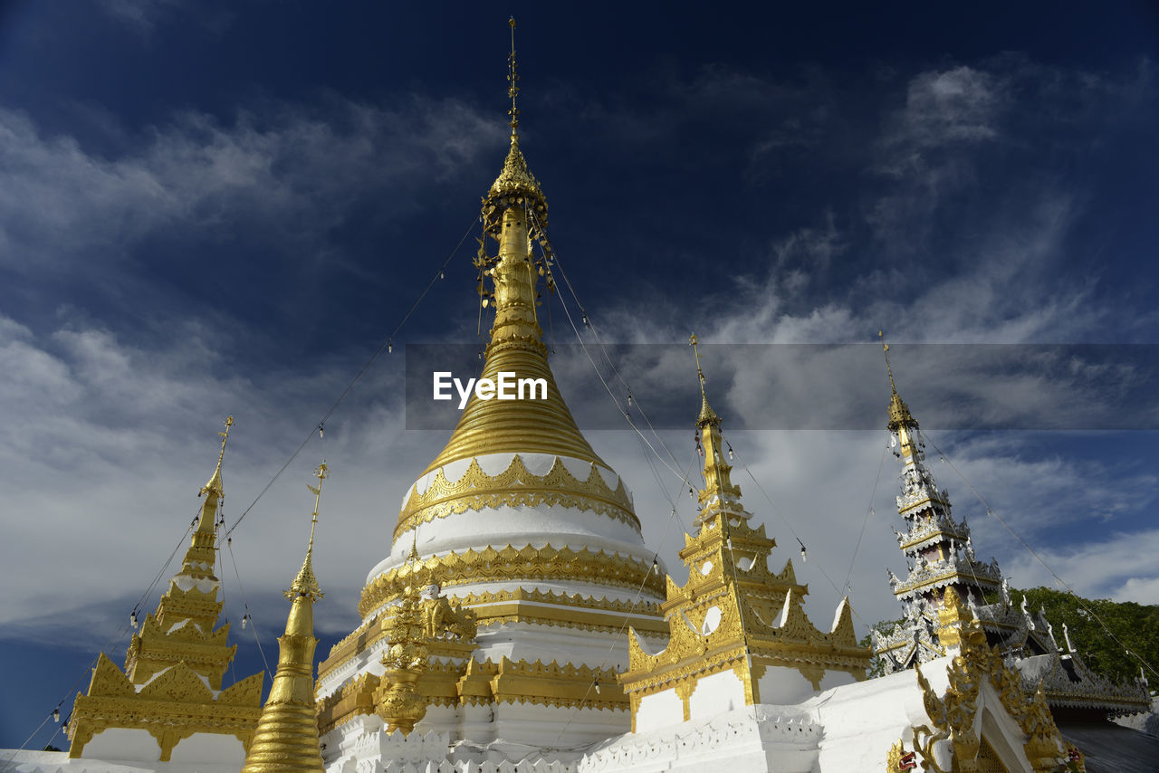 religion, spirituality, place of worship, pagoda, sky, gold colored, architecture, travel destinations, built structure, building exterior, low angle view, cloud - sky, shrine, ancient, day, no people, outdoors, nature