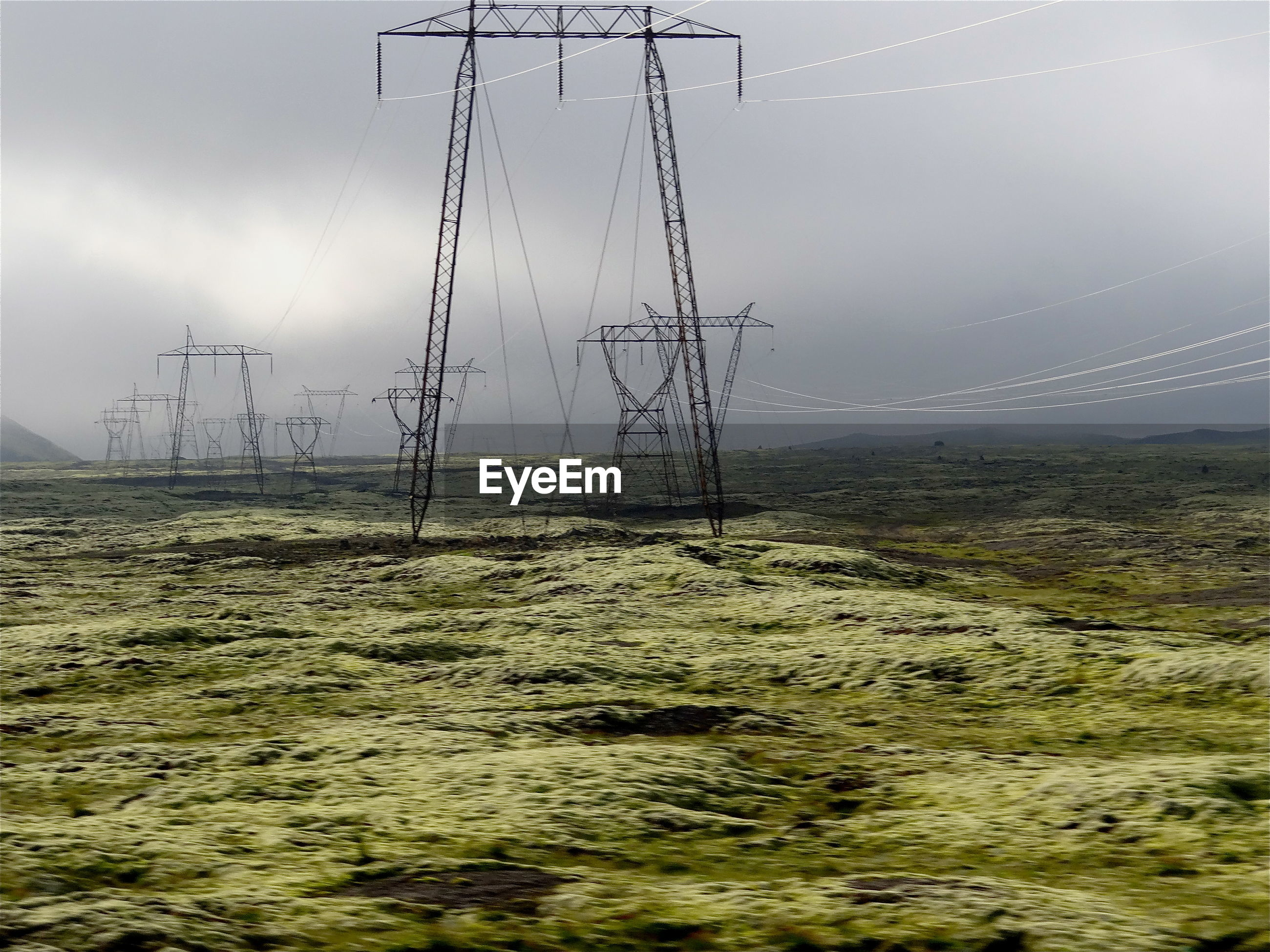Electricity pylons on field against cloudy sky