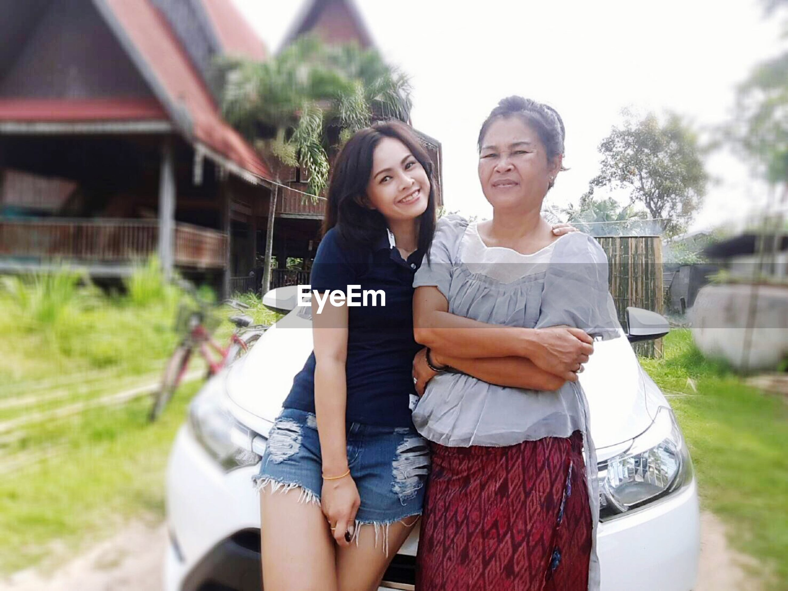real people, young women, two people, young adult, leisure activity, three quarter length, casual clothing, happiness, smiling, looking at camera, togetherness, lifestyles, front view, outdoors, day, built structure, standing, beautiful woman, architecture, building exterior, portrait, bonding, tree, people