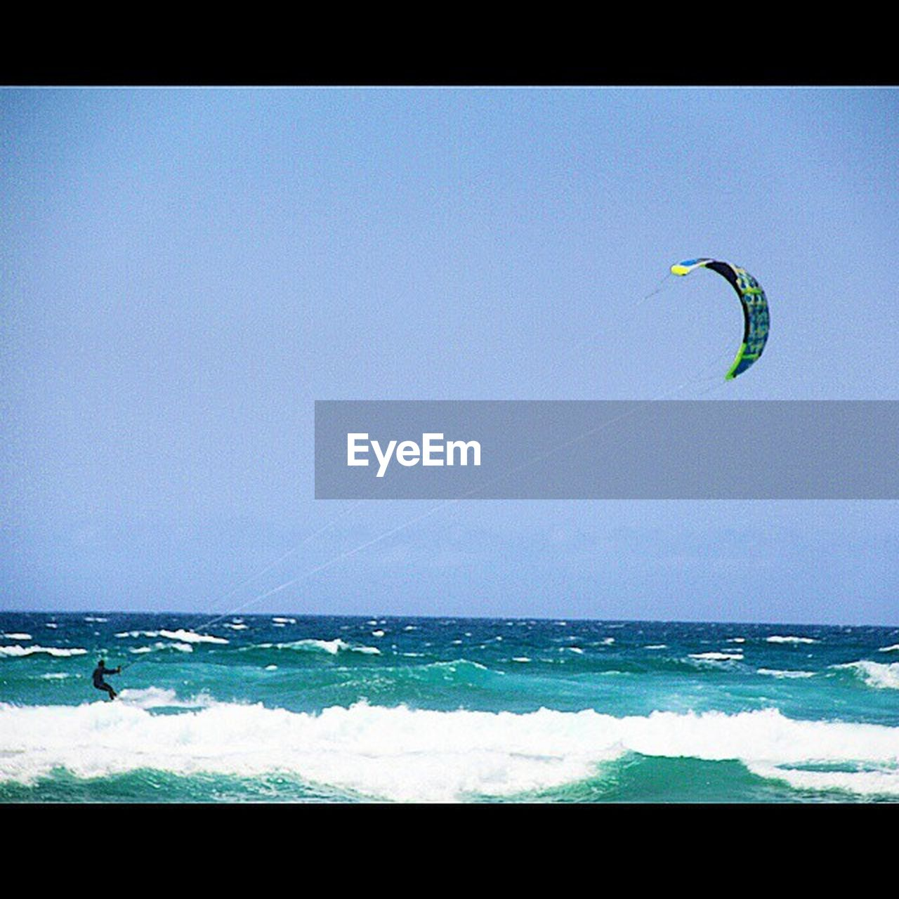 sea, extreme sports, horizon over water, sport, adventure, wave, kiteboarding, nature, leisure activity, water, one person, vacations, scenics, surfing, motion, day, beach, blue, outdoors, beauty in nature, sky, parachute, real people, paragliding, one man only, people