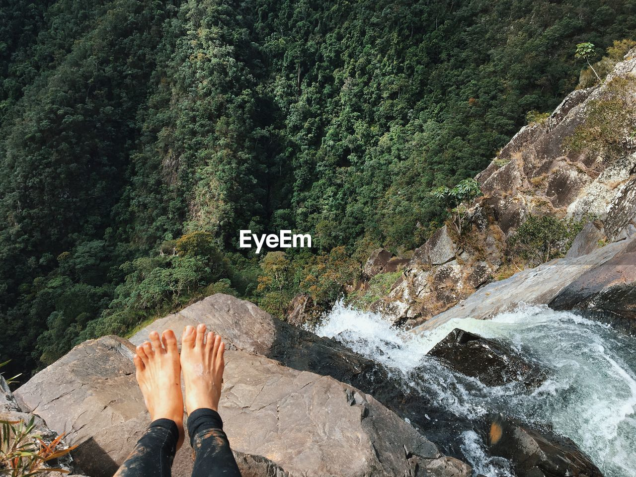 LOW SECTION OF PERSON STANDING BY WATERFALL ON ROCK